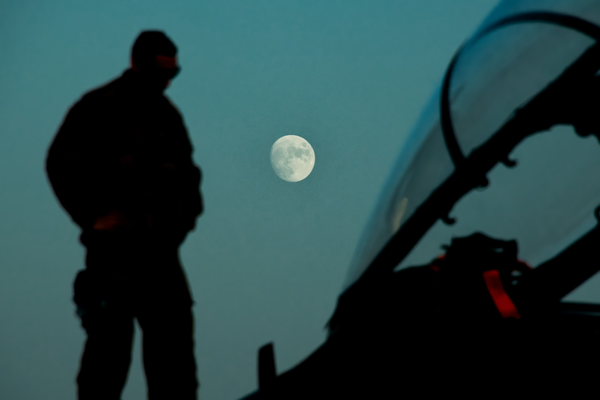 A maintainer deployed to the 332d Air Expeditionary Wing, checks an F-15E Strike Eagle during a routine post flight inspection Sept. 29, 2020, as the moon rises over the flightline in an undisclosed location. (Master Sgt. Jonathan Young/Air National Guard)
