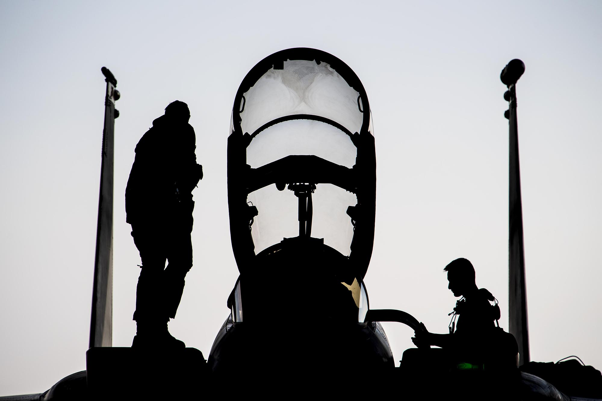 Air Force Capt. Ryan Heil and a maintainer assigned stand on an F-15E Strike Eagle shortly after landing at Al Dhafra Air Base, United Arab Emirates, Feb 13, 2021. (Senior Airman Aaron Larue Guerrisky/Air Force)
