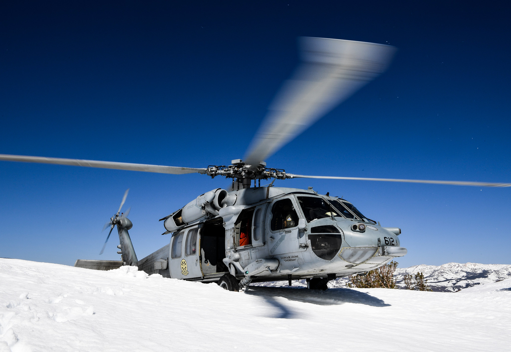 An MH-60S Seahawk helicopter lands in the snow during high-altitude landing training, hosted by Naval Aviation Warfighting Development Center (NAWDC) at Naval Air Station Fallon, Nev., on April 1, 2021. (Chief Mass Communication Specialist Shannon Renfroe/Navy)