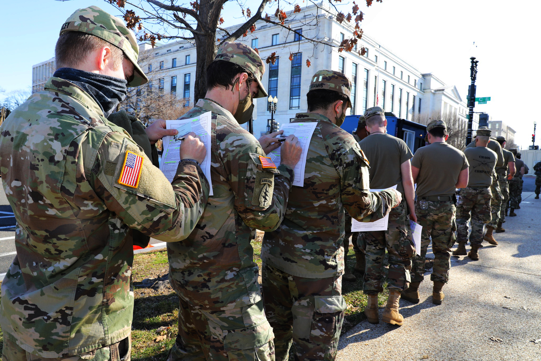 Soldiers in the Maryland Army National Guard use the back of the soldier in front of them to fill out their medical paperwork to receive the COVID-19 vaccine at the U.S. Capitol Complex in Washington on Jan. 14, 2021. (Sgt. Chazz Kibler/National Guard)