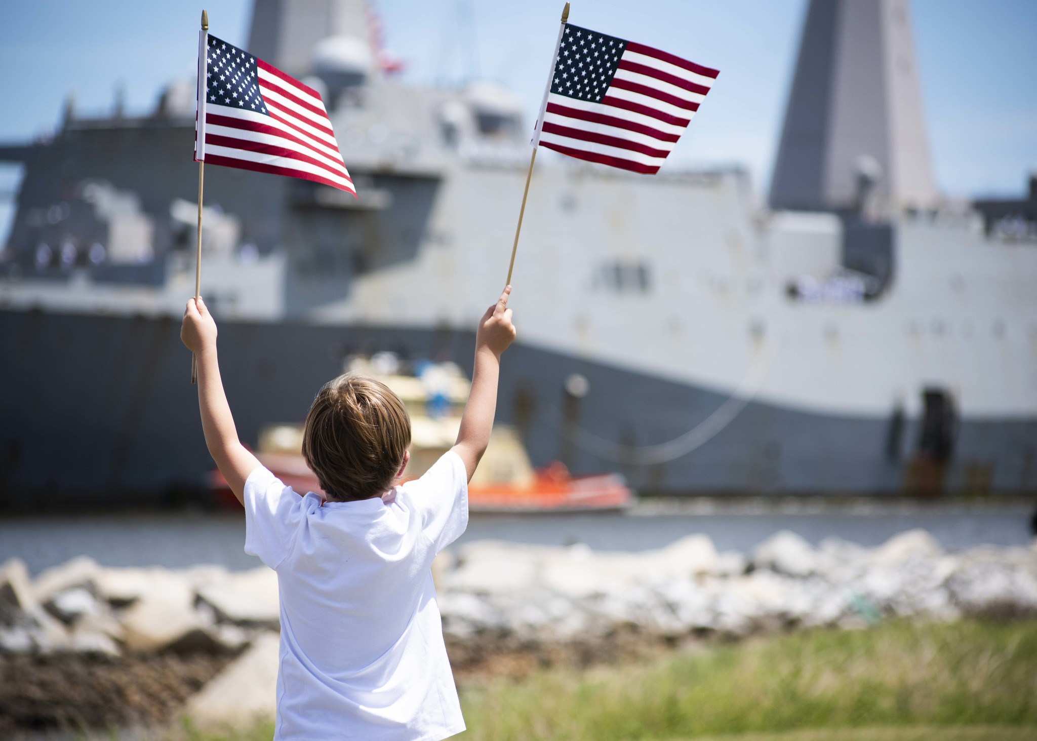 A family member waives American flags as the San Antonio-class amphibious transport dock ship USS New York (LPD 21) arrives at Naval Station Mayport in Florida on July 28, 2020. (MC1 Brian G. Reynolds/Navy)