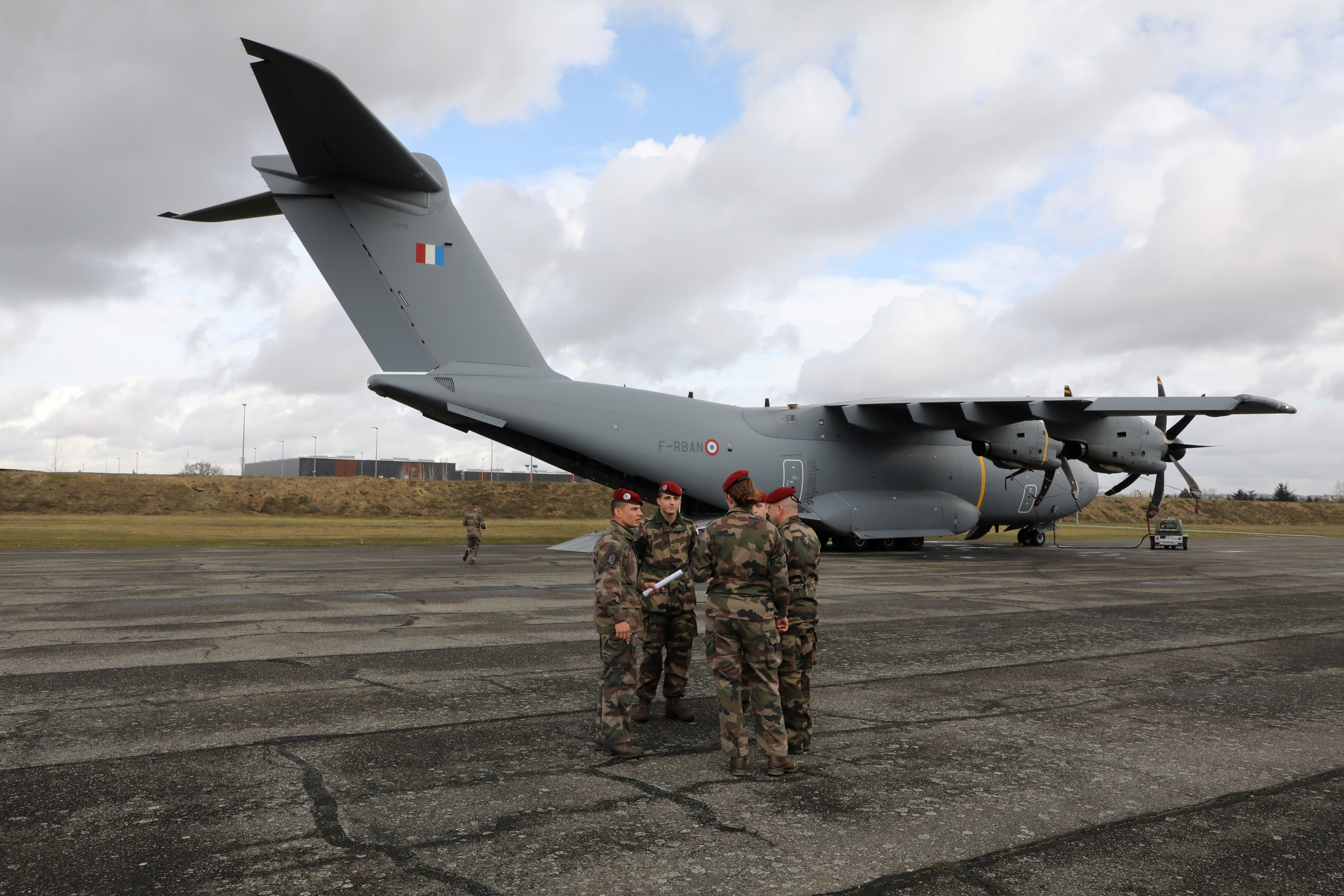 French soldiers stand next to an Airbus A400M on the tarmac at the air force base 101 Toulouse-Francazal, in Toulouse, southern France, on Jan. 17, 2019, before the French president's visit to deliver his 2019 New Year's wishes to the military forces. (Photo by Ludovic Marin/AFP/Getty Images)