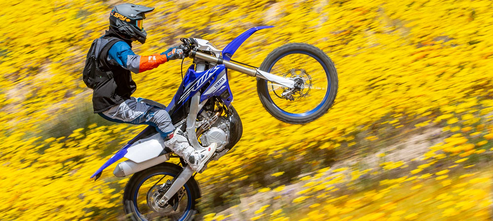 Biker doing wheelie in flowers with 2019 Yamaha WR450F.