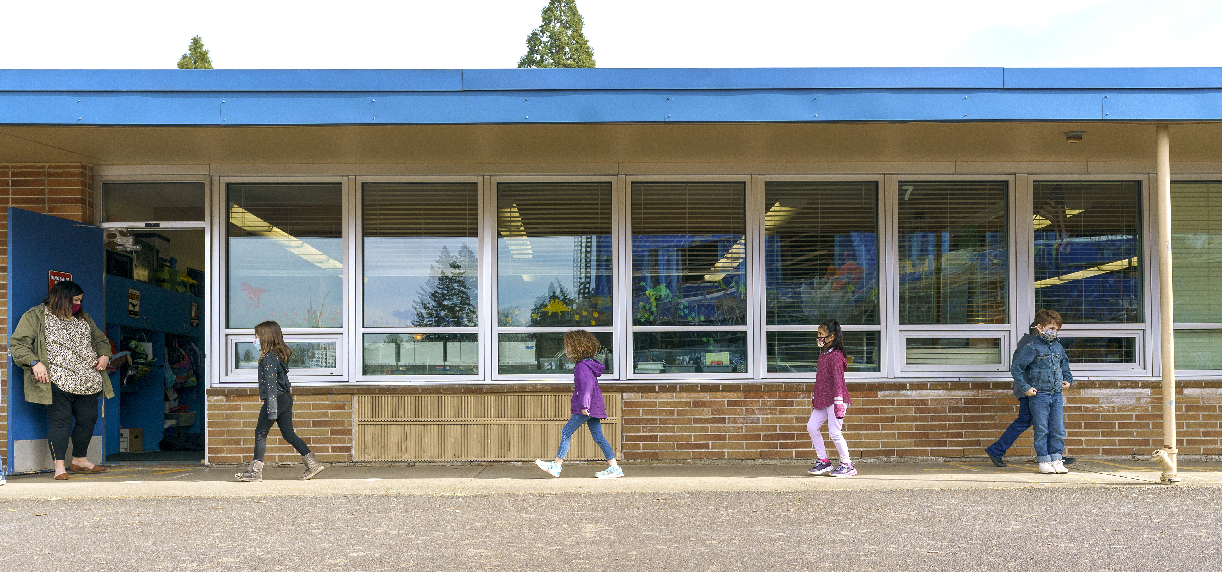 kids walking outside their school building, with a long row of windows behind them