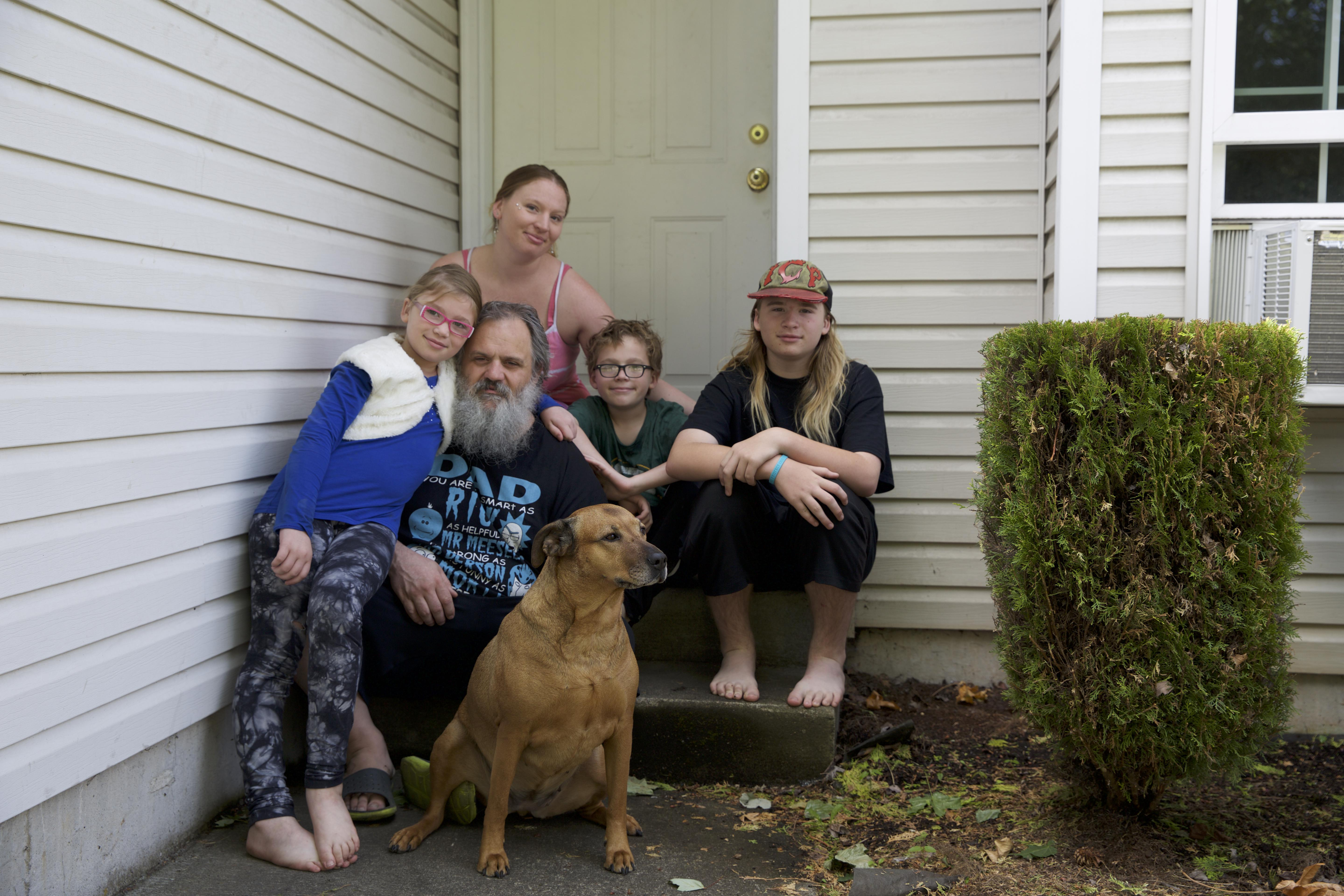AndaKiss, Britney, Tank, Talin, and Kenny Dunham, along with their dog Lucy, on the front steps of their home.