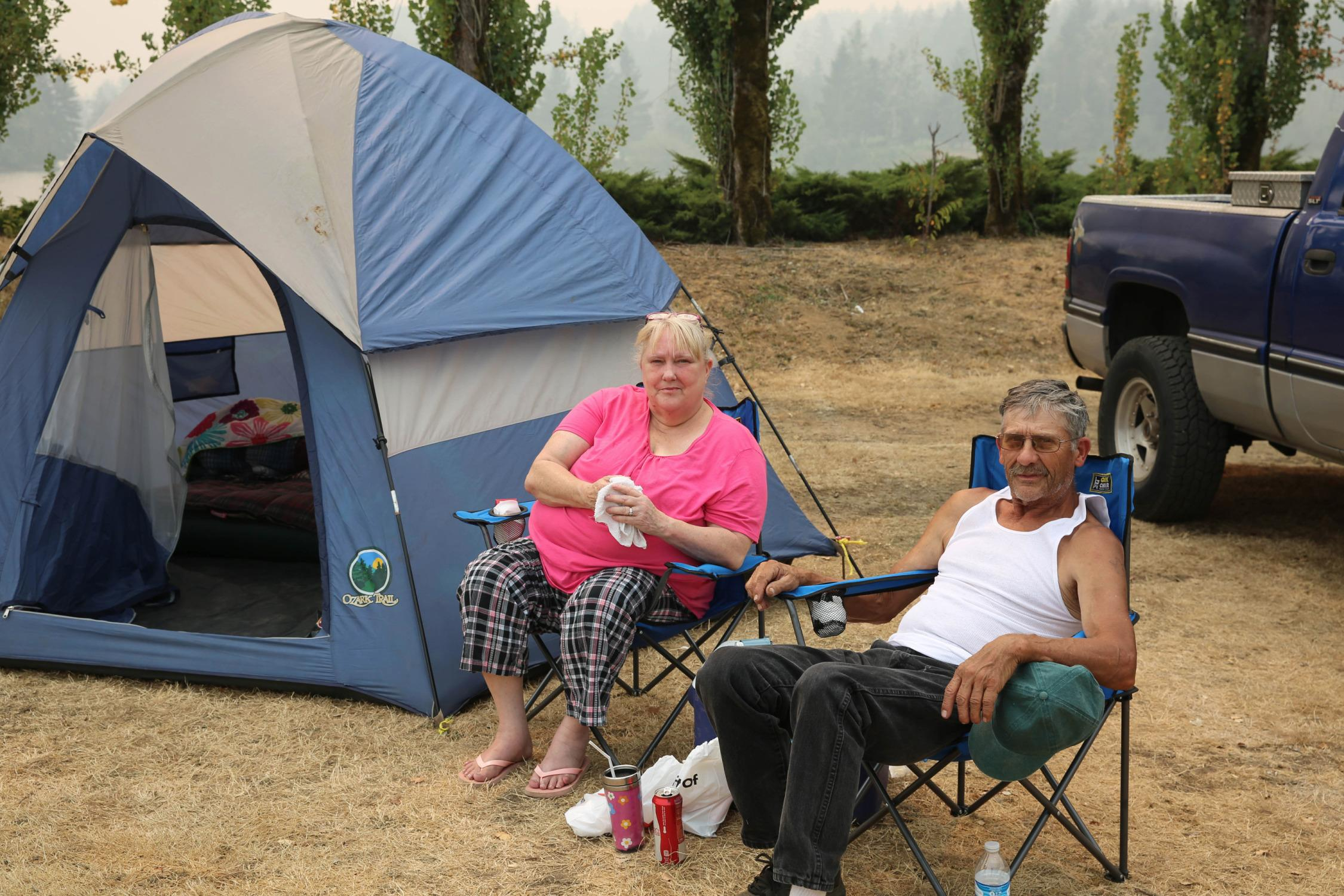 """Larry and Tammy South live in a trailer court in Cascade Locks that was evacuated. The town has been home for the last 36 years. Tammy holds a rag over her mouth to block out the thick smoke. """"I'm still scared,"""" South said."""