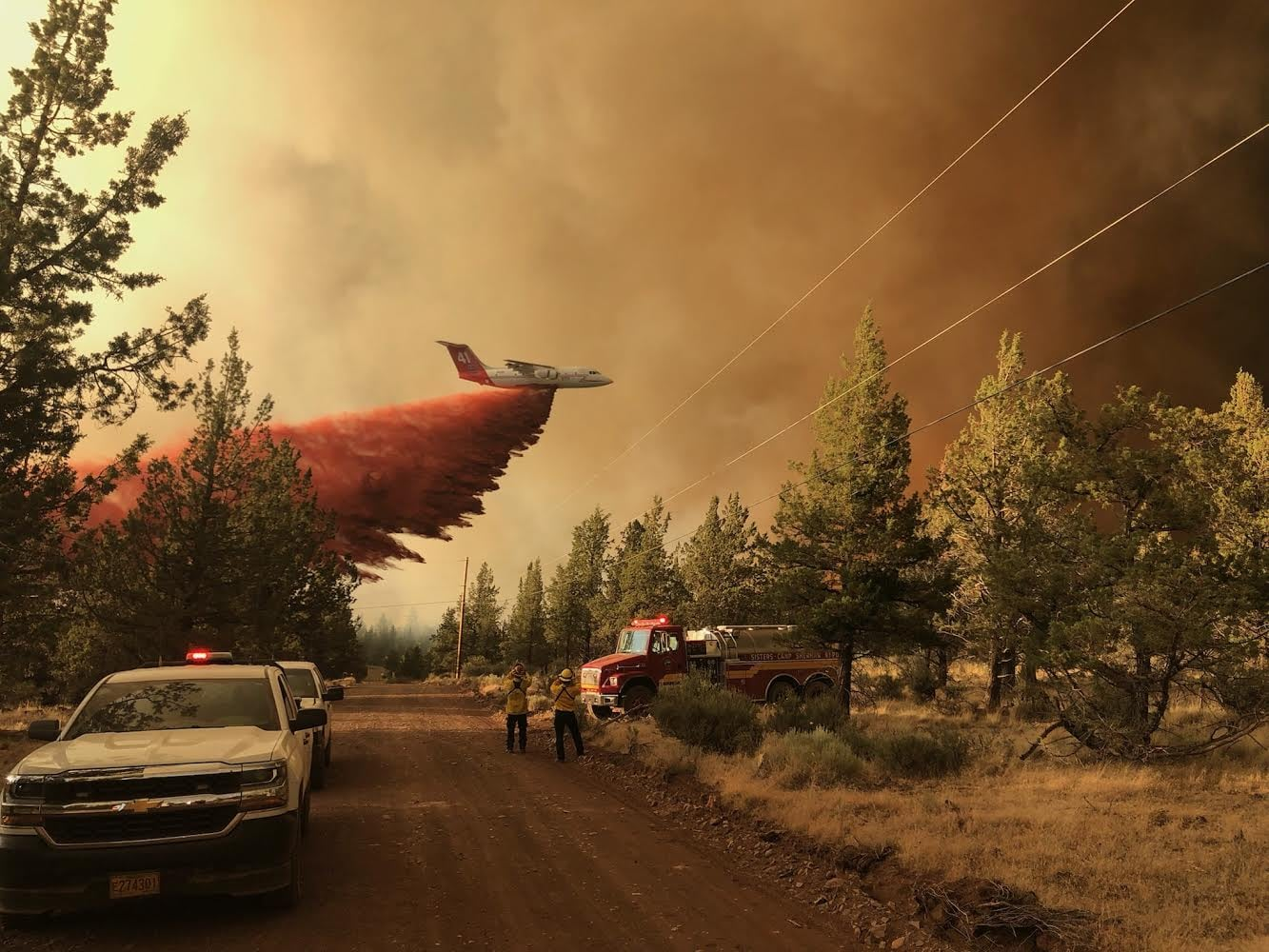 An airplane drops a large plume of reddish pink fire retardant as it flies over trees. A fire truck and police vehicle are in the foreground. Dark heavy wildfire smoke fills much of the sky.