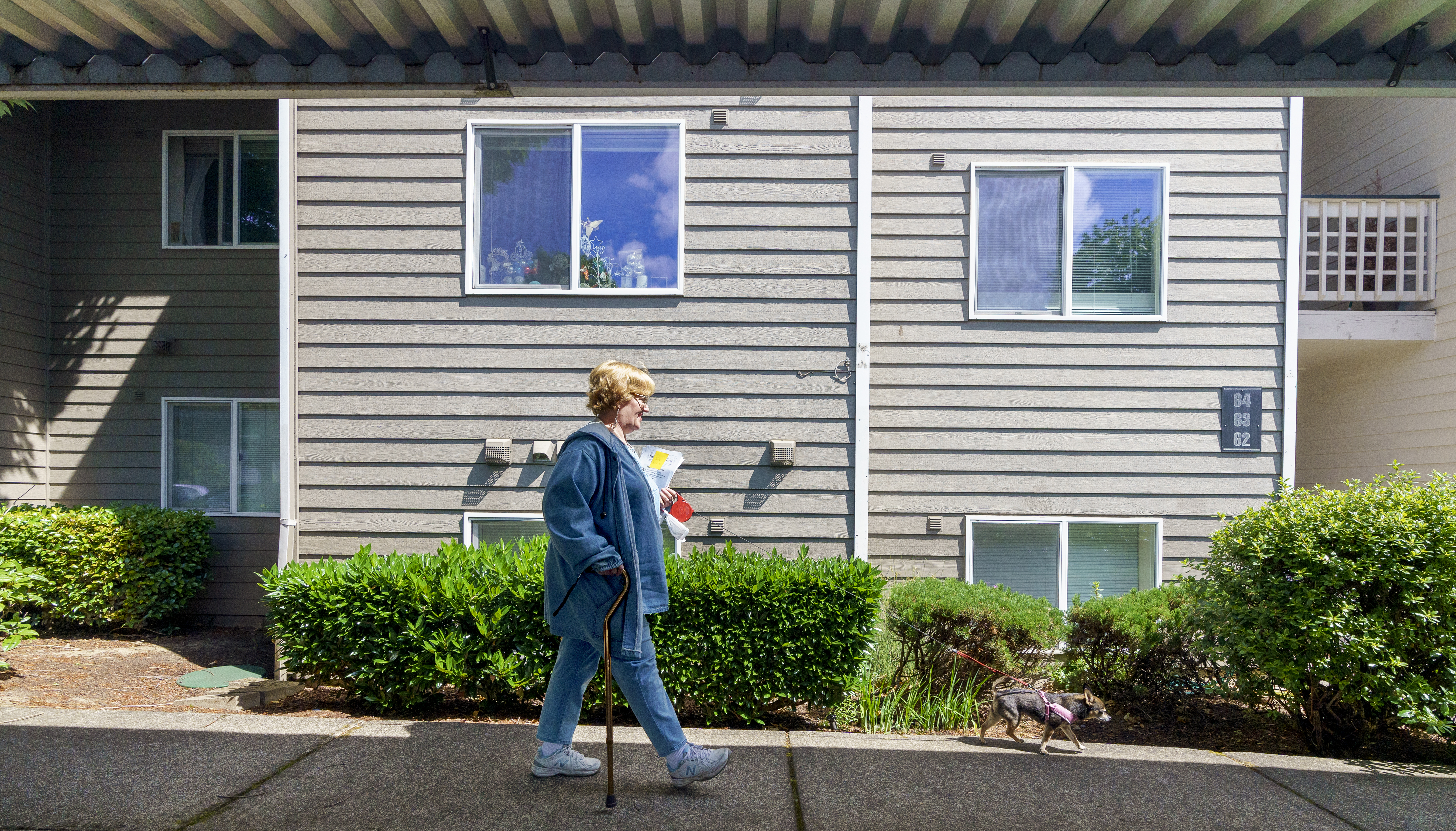 Heidi Johnstone, 61, distributes a newsletter and meeting summary of the Woodspring Tenants Association through the affordable housing senior resident complex in Tigard, June 12, 2021. The real estate investment company Hamilton Zanze announced in January that all of the 172-units will be brought to market rate within a few years.