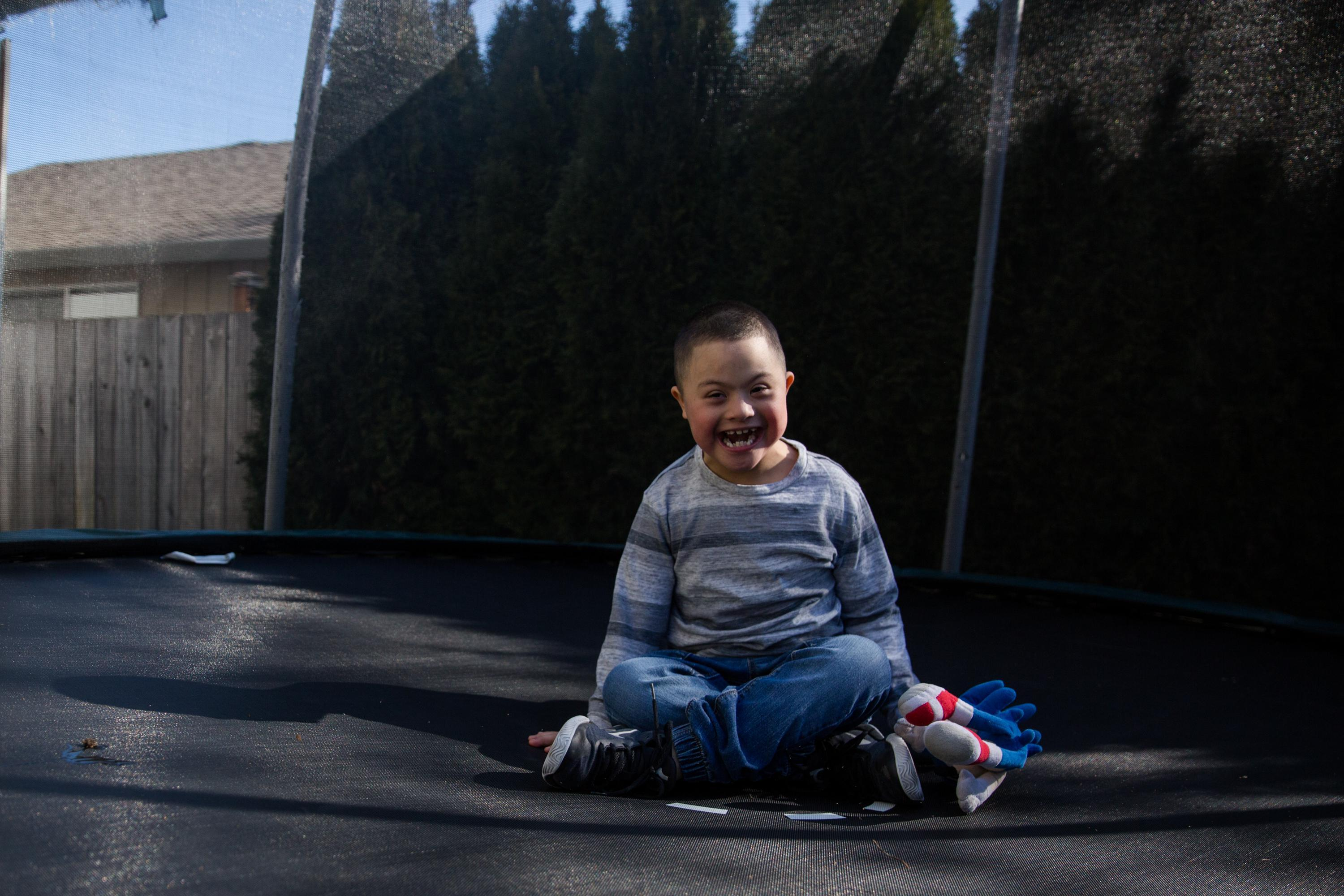 Romeo, 7, jumps on a trampoline in the backyard of his family home in Vancouver, Wash., Saturday, March 2, 2019. Romeo has Down syndrome and his family has struggled to find adequate care from schools in southwest Washington.