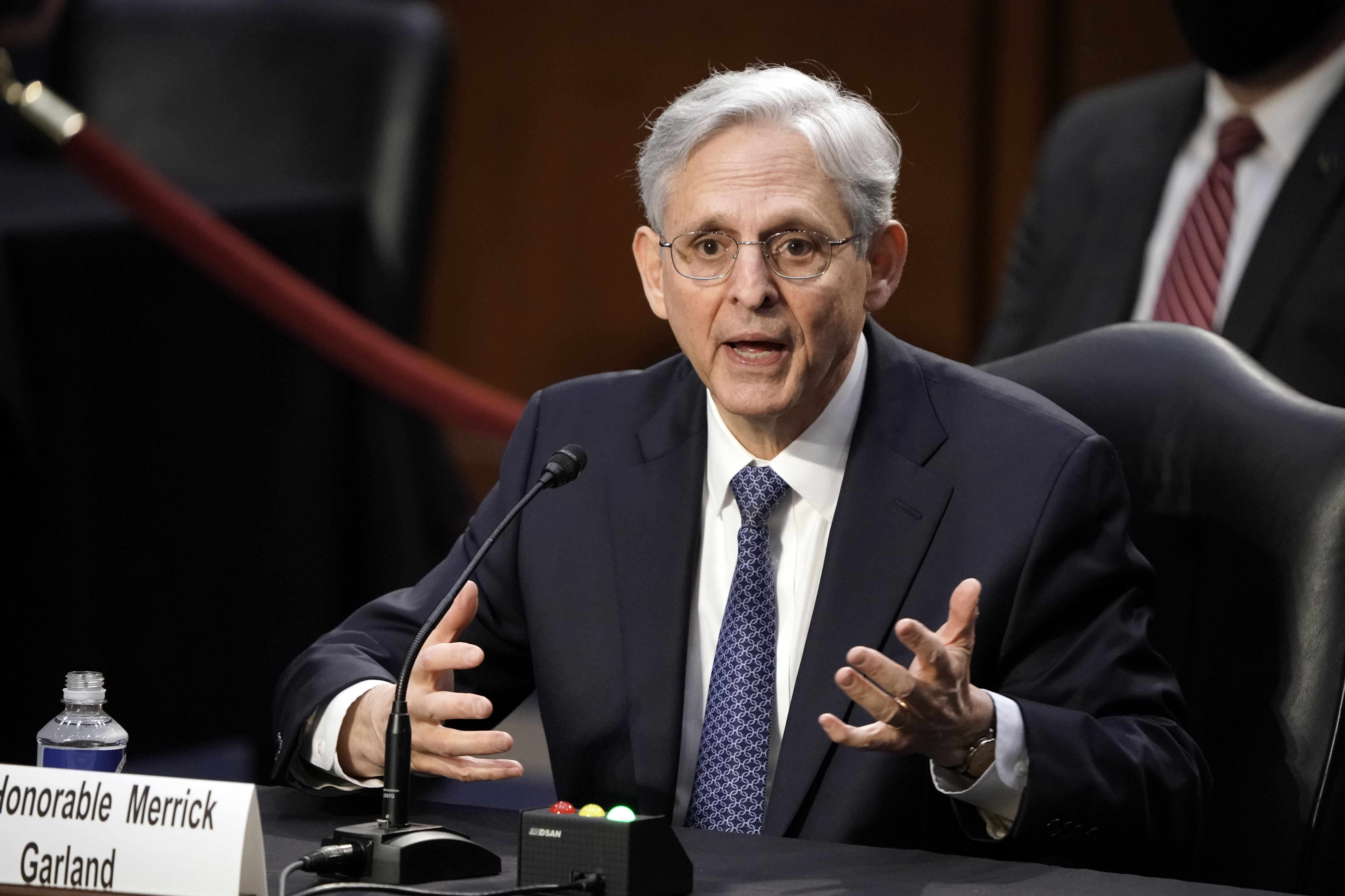 """A man wearing a suit sits behind a table and speaks into a microphone. A sign on the desk reads """"Honorable Merrick Garland"""""""