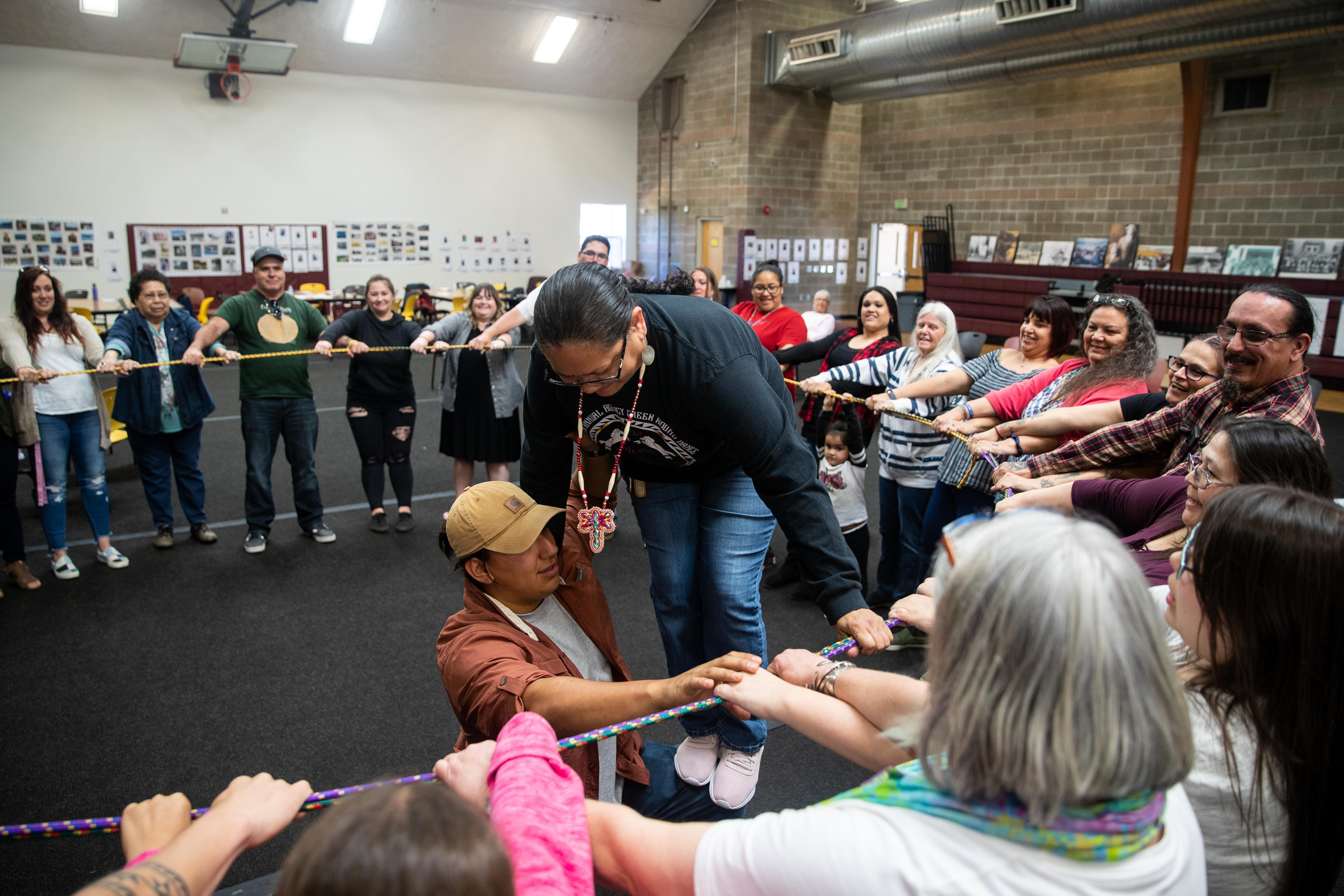 Josh Cocker helps Kimberly Contreras gain her balance on the ropes. This exercise is meant to deepen the community's understanding of interdependency.