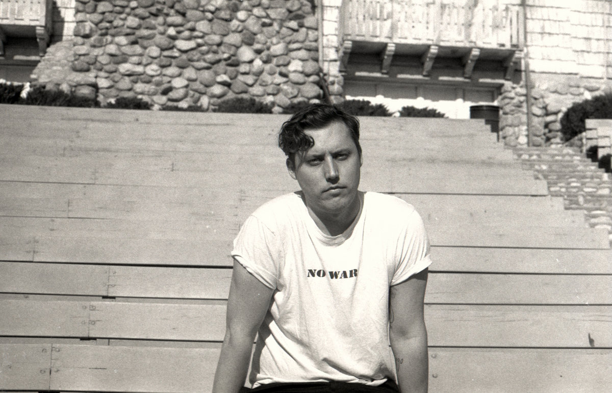 """A man wears a T-shirt that reads """"NO WAR"""" and stares at the camera in this black-and-white photo."""