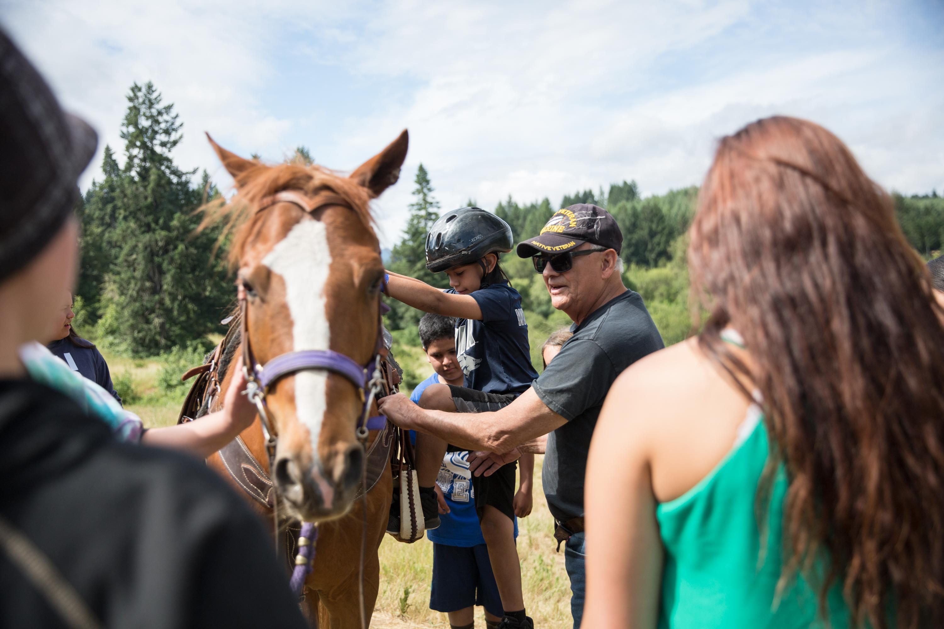 John Spence helps a boy onto his horse, Koda, during the connection to horses session at Wellness Warrior Camp in Grand Ronde, Ore., on Wednesday, June 24, 2019.