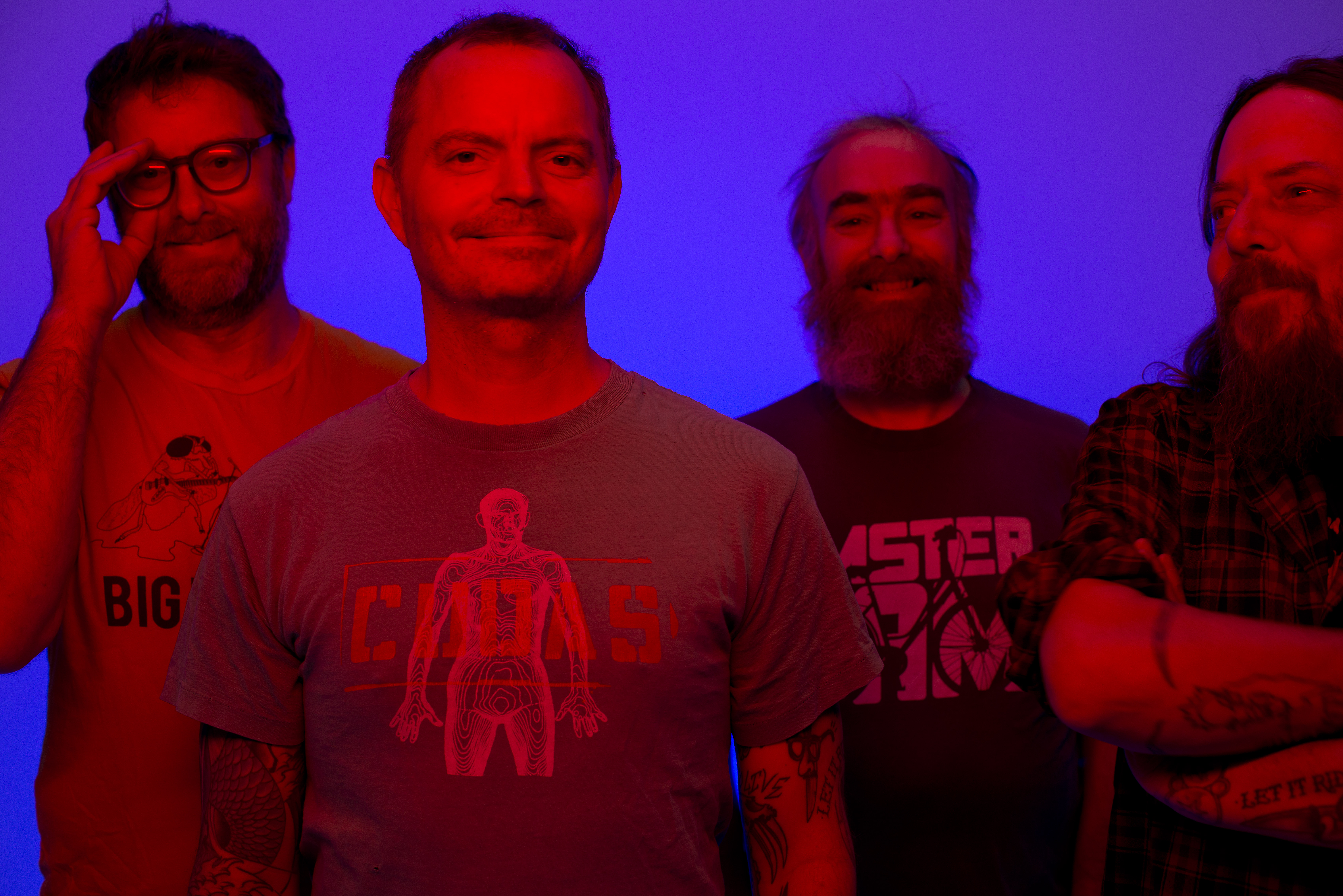 Four people stand together with slight smiles on their faces. The lighting is distorted so they appear to be very reddish in color, and the background is a bright purplish blue.