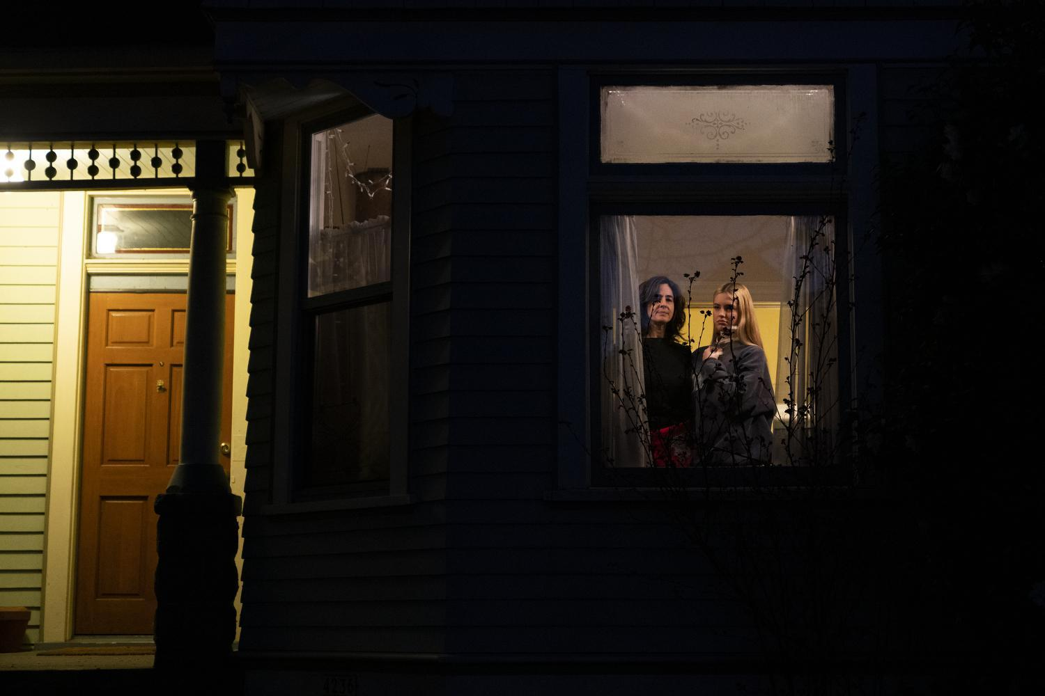 Brynna Sibilla and her daughter Talia in the window of their home in Portland, Ore., March 16, 2020.