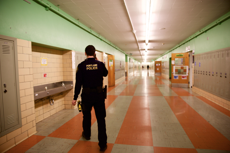 Officer Carlos Ibarra, a school resource officer, walks through the halls of Madison High School in Northeast Portland.