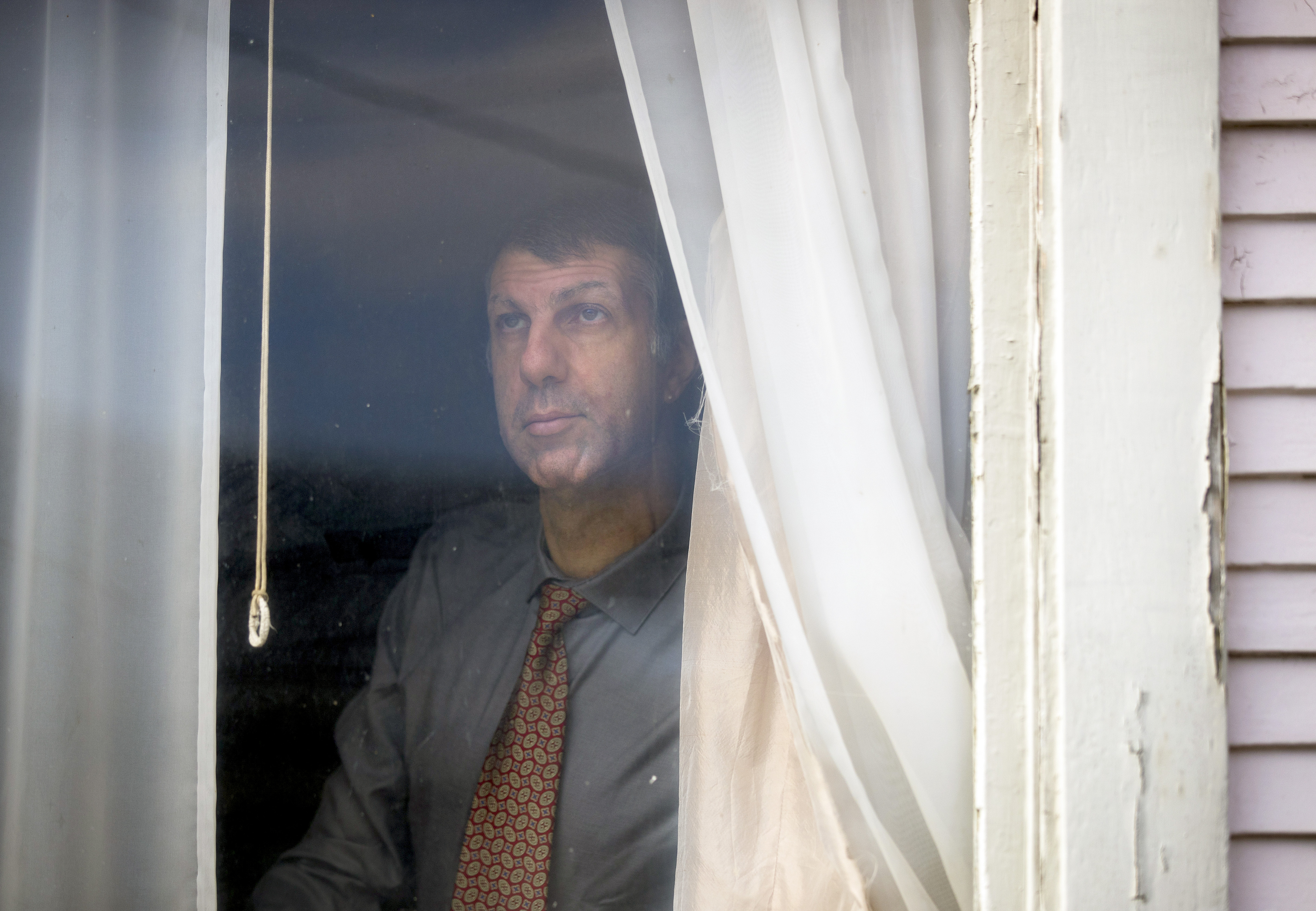 Joe Dibee is portrayed while looking out of a window at his family's home on Wednesday, February 17, 2021, in Seattle.