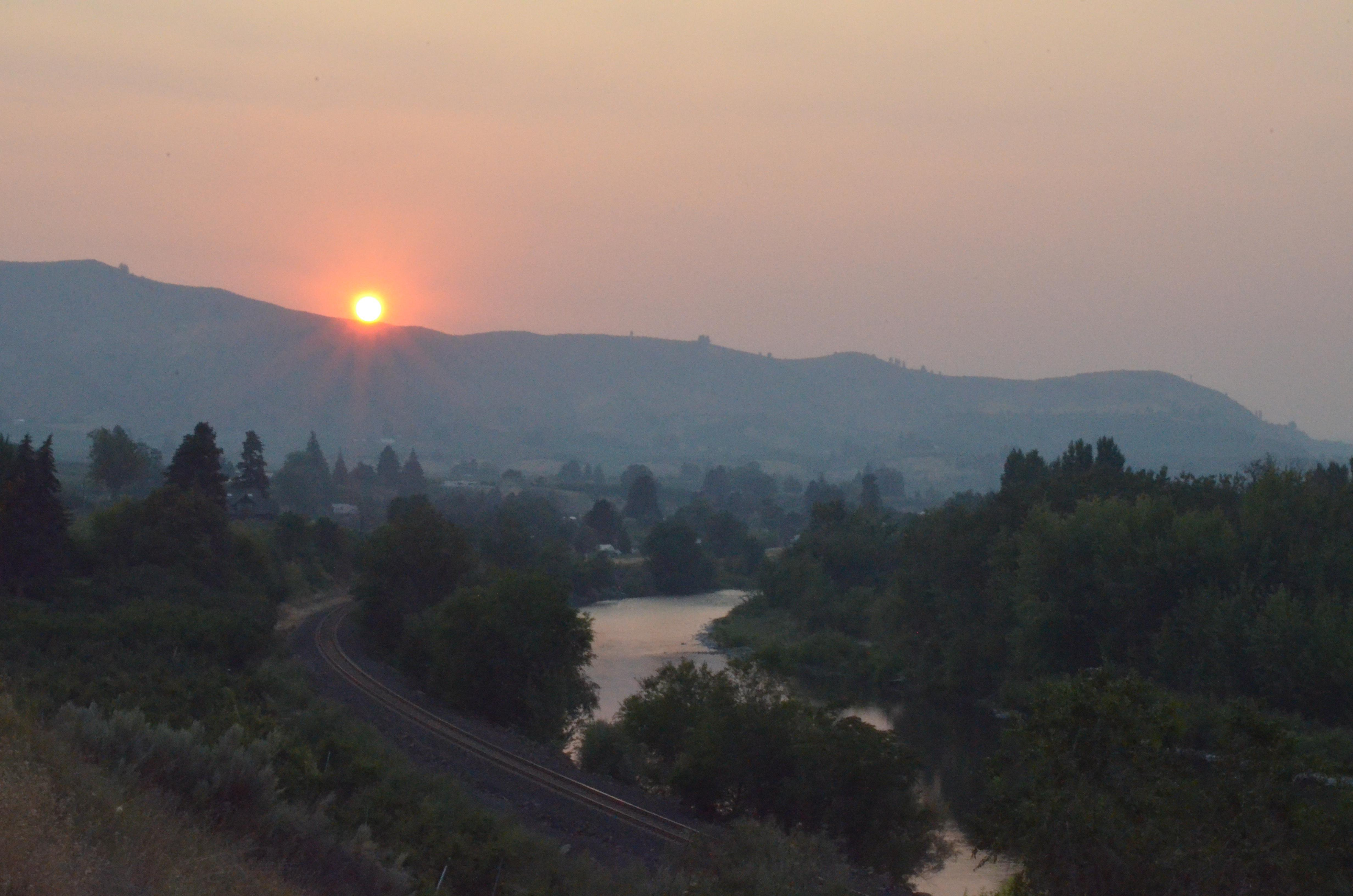 Hazy skies caused by wildfire smoke are creating increasingly common scenes like this in Eastern Washington' above the Wenatchee River in August, 2018.