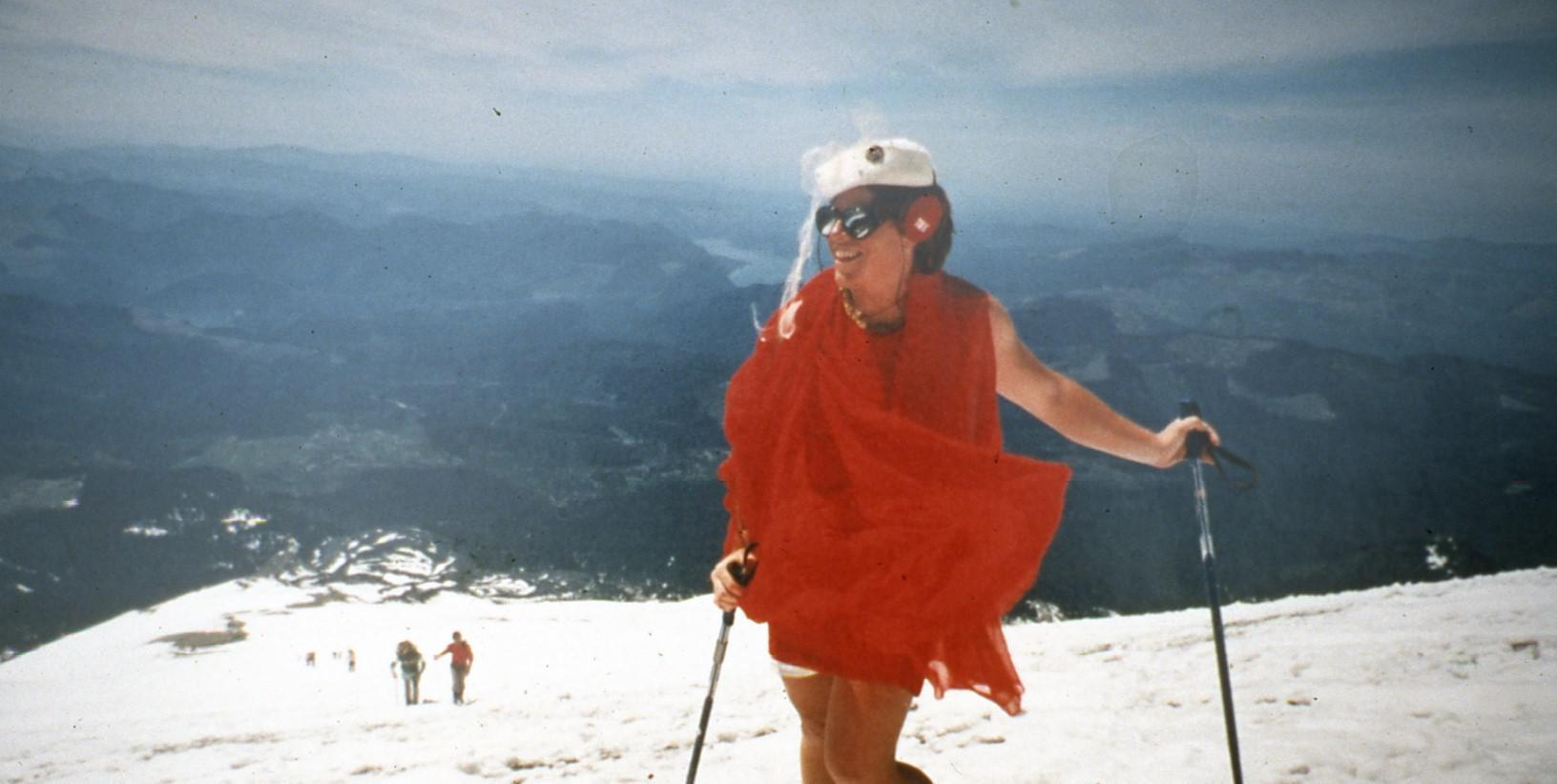 Kathy Phibbs stands on the summit of Mount St Helens in a red chiffon dress and pillbox hat after the mountain reopened to climbers in 1987.