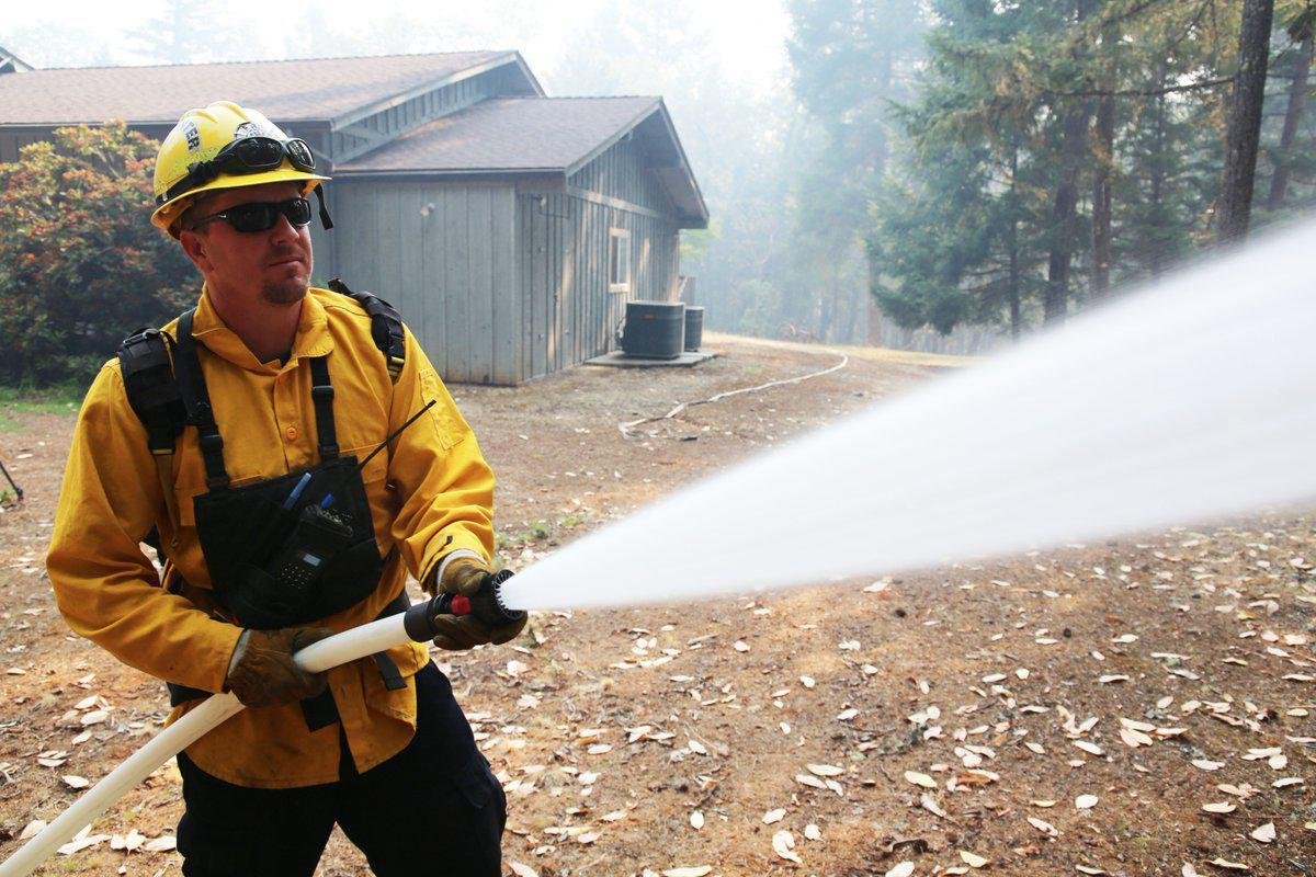 Klamath County firefighter Jeff Frost runs a structure protection drill at a home on a secluded cul-de-sac near the Rogue River. Its owners evacuated as the Taylor Creek Fire burned closer.