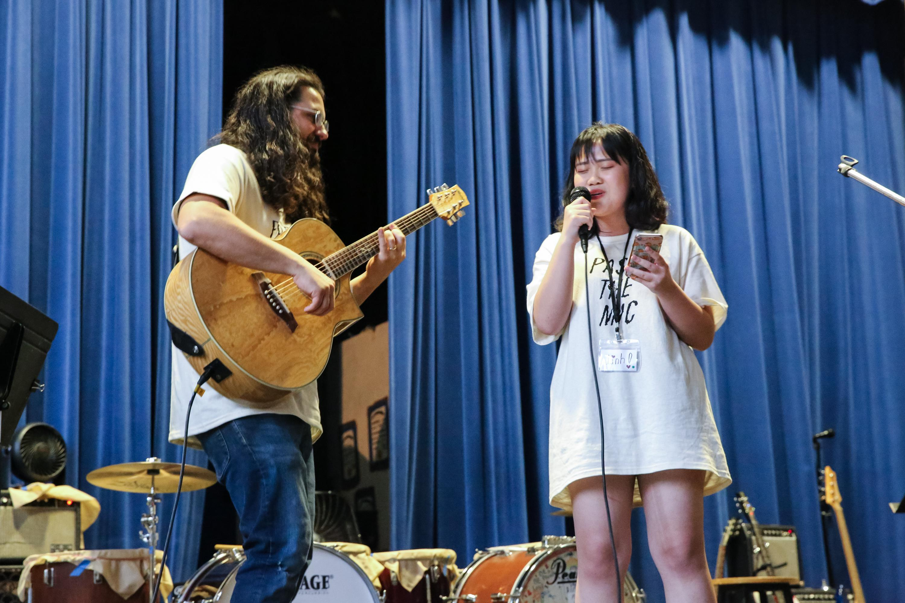 Linh Doan, right, sings her song for the Pass the Mic concert in Portland, Ore., Friday, Aug. 2, 2019. Sam Adams, left, of Portland band Sama Dams provides backing guitar.