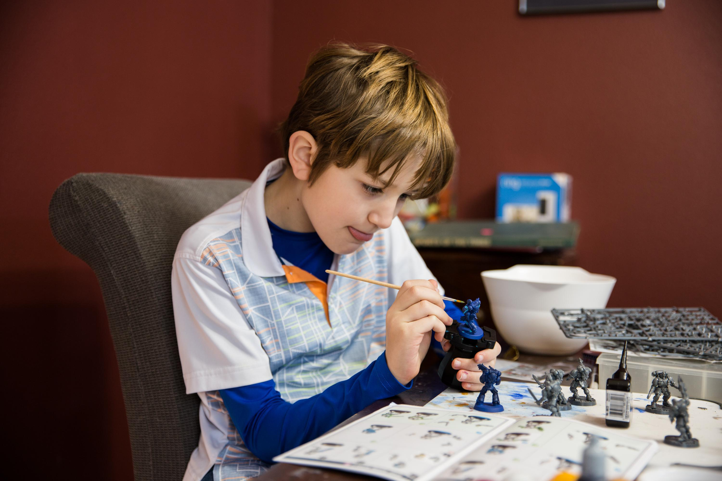 Ten-year-old Landon paints a model at his family's dining room table in Vancouver, Wa., Thursday, Feb. 28, 2019.