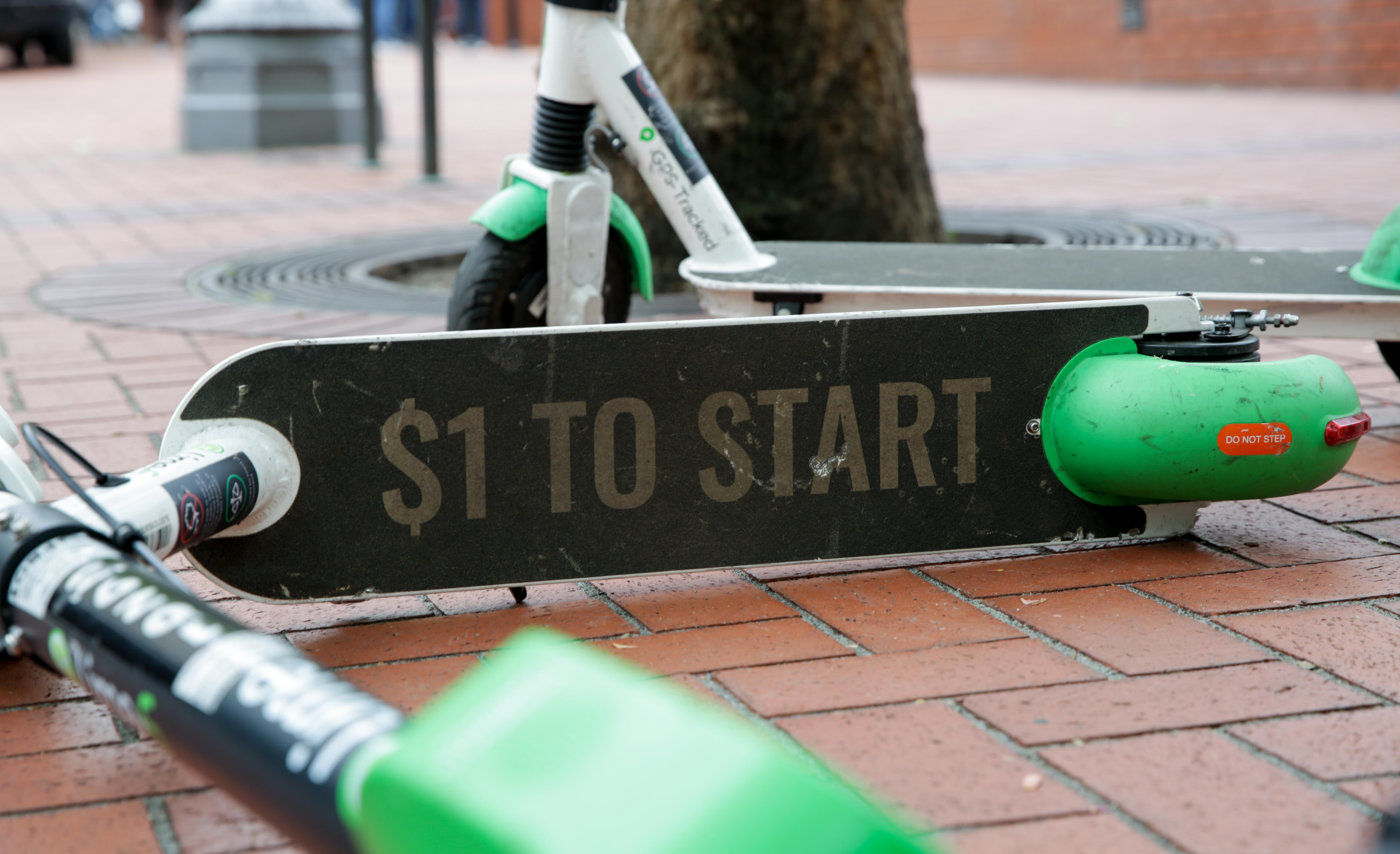 An electric LIME scooter lays on its side on the sidewalk at Pioneer Courthouse Square in Portland, Ore., on Friday, May 20, 2019.
