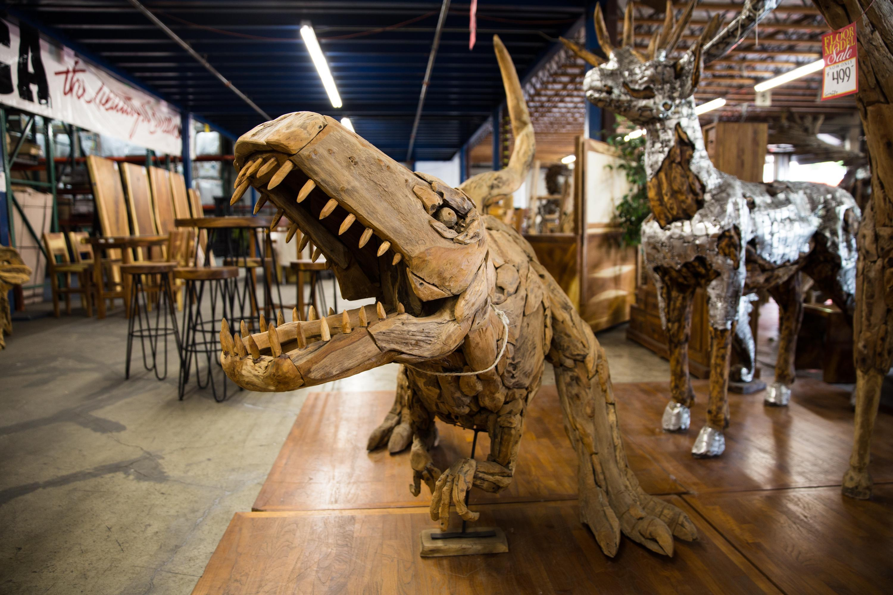 A teak dinosaur hand carved in Indonesia guards the floor at America the Beautiful Dreamer furniture store in Vancouver, Wash., Friday, June 27, 2019. Owner Don Thompson said roughly 40% of his shoppers came from Oregon prior to the sales tax change.