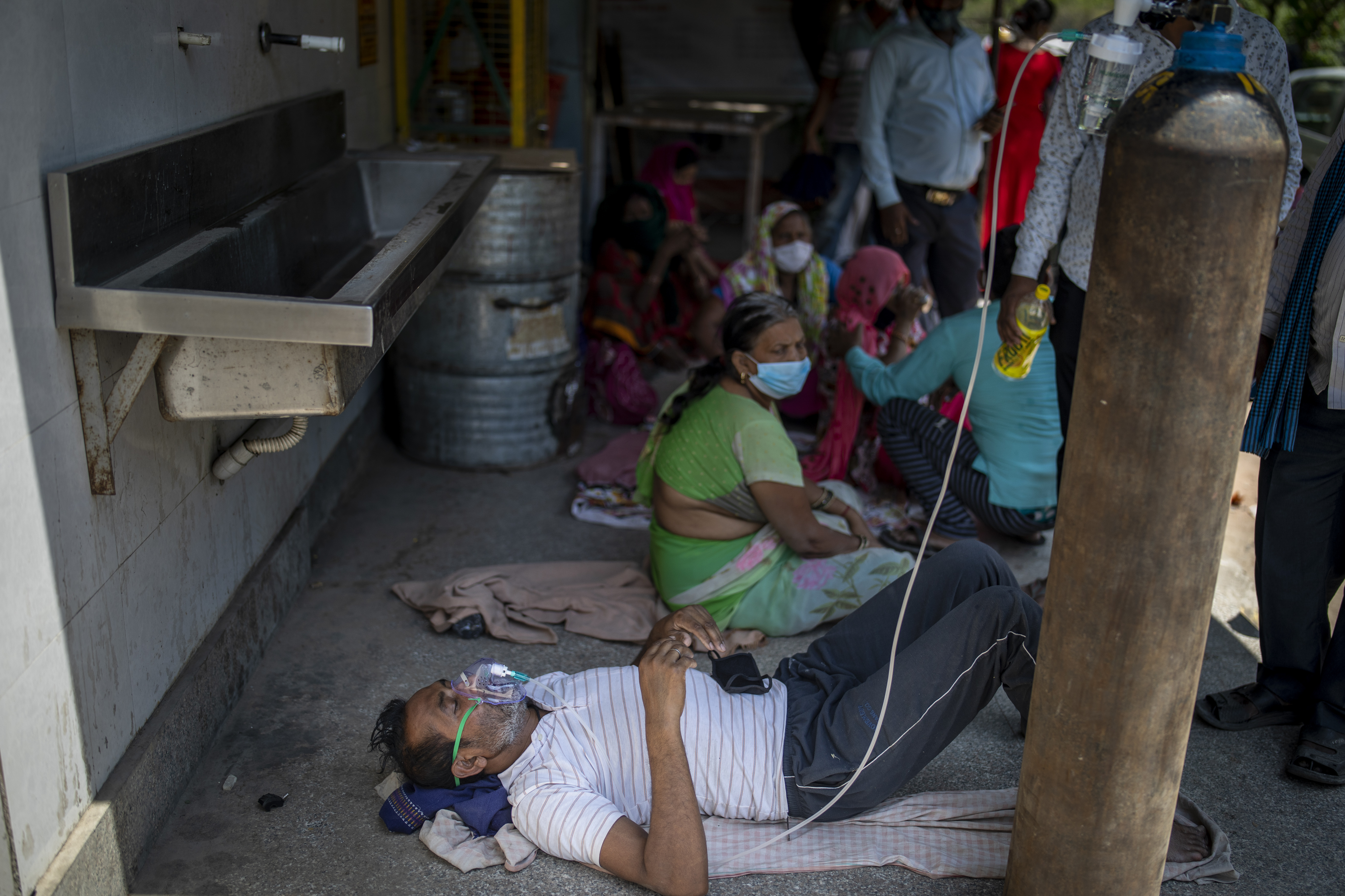 A patient receives oxygen outside a gurdwara, a Sikh house of worship, in New Delhi, India, Saturday. India's medical oxygen shortage has become so dire that this gurdwara began offering free breathing sessions with shared tanks to COVID-19 patients waiting for a hospital bed.