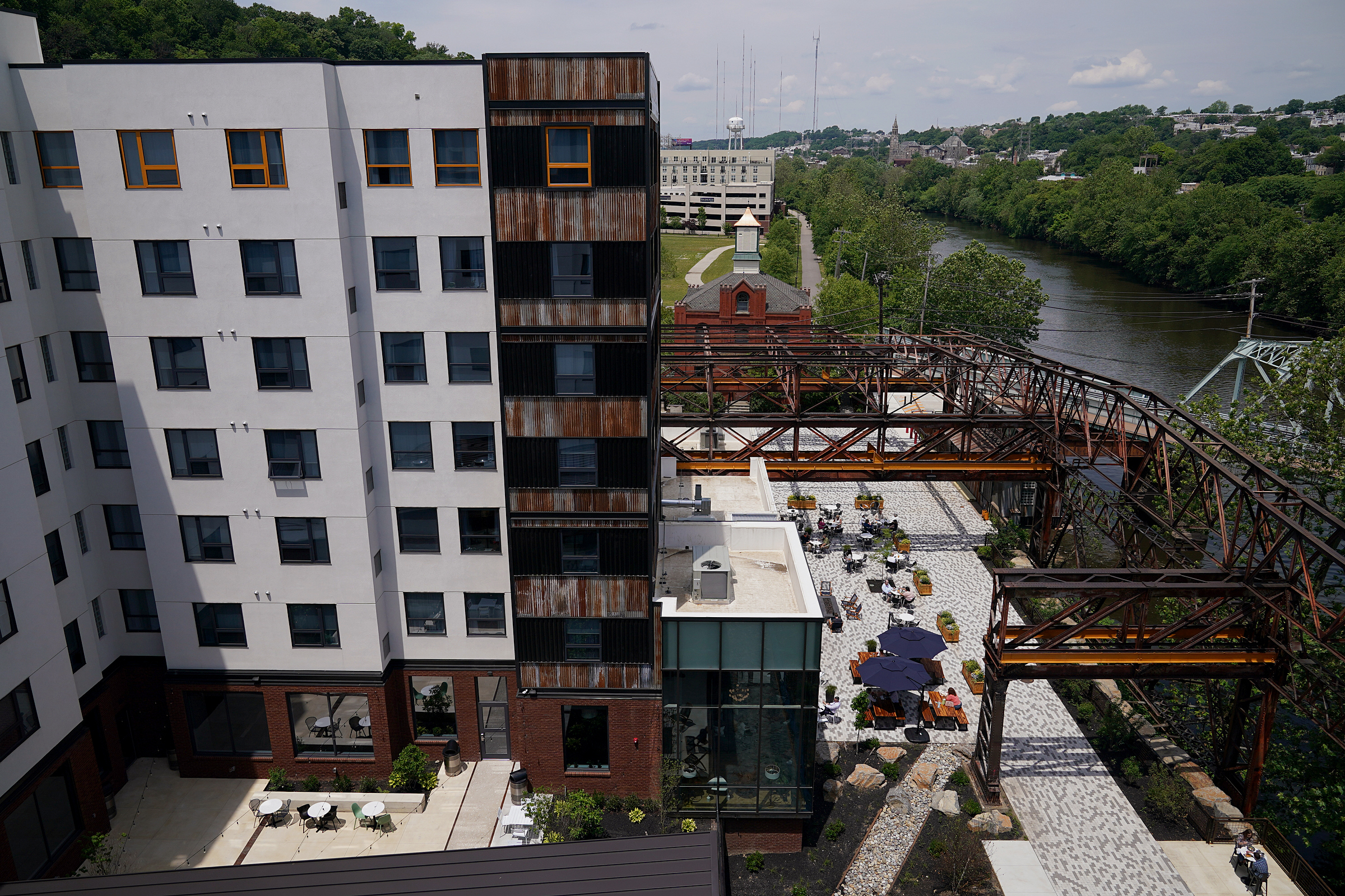 A Residence Inn hotel (left) and outdoor dining area for The Landing Kitchen are pictured at the Ironworks at Pencoyd Landing in Bala Cynwyd, Pa., on Wednesday, June 2, 2021. The new development, which opened earlier this year with a restaurant and hotel, is located on the site of the former Pencoyd Iron Works along the Schuylkill.