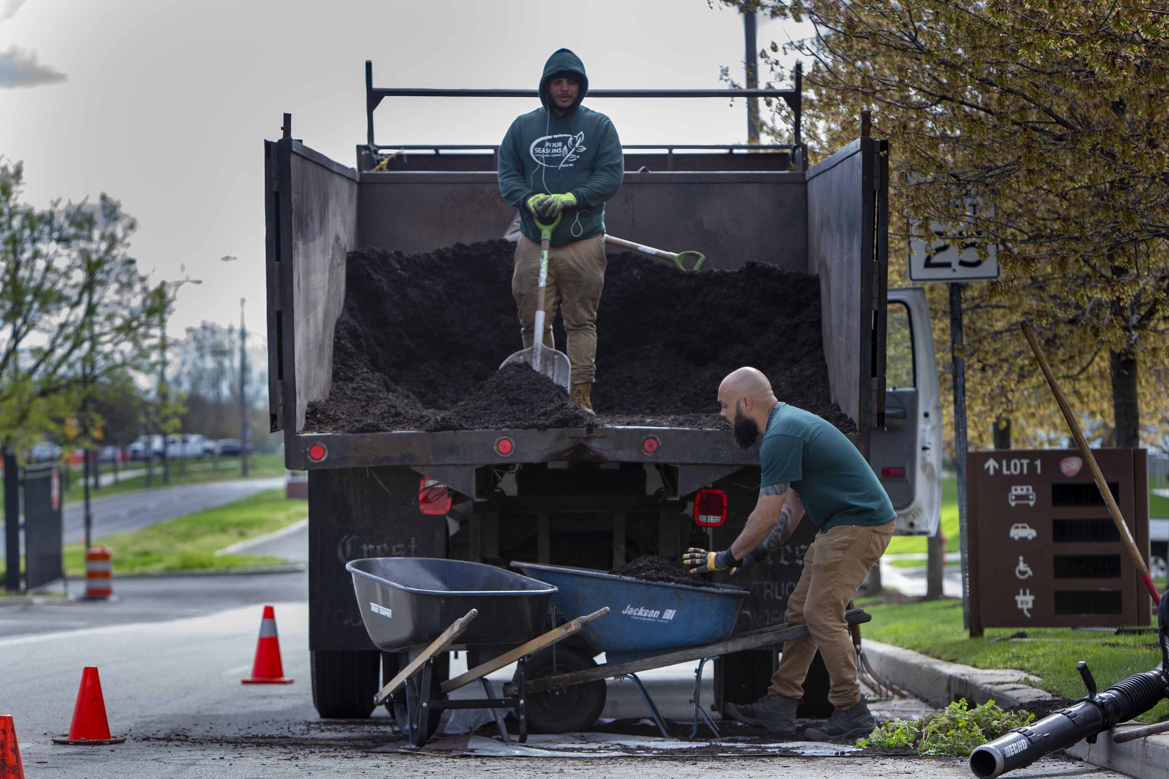 Cameron Corbett removes mulch from a Four Seasons Total Landscaping truck for the flower beds at Navy Yard. On the truck is fellow Four Seasons worker Richard Vanhart.