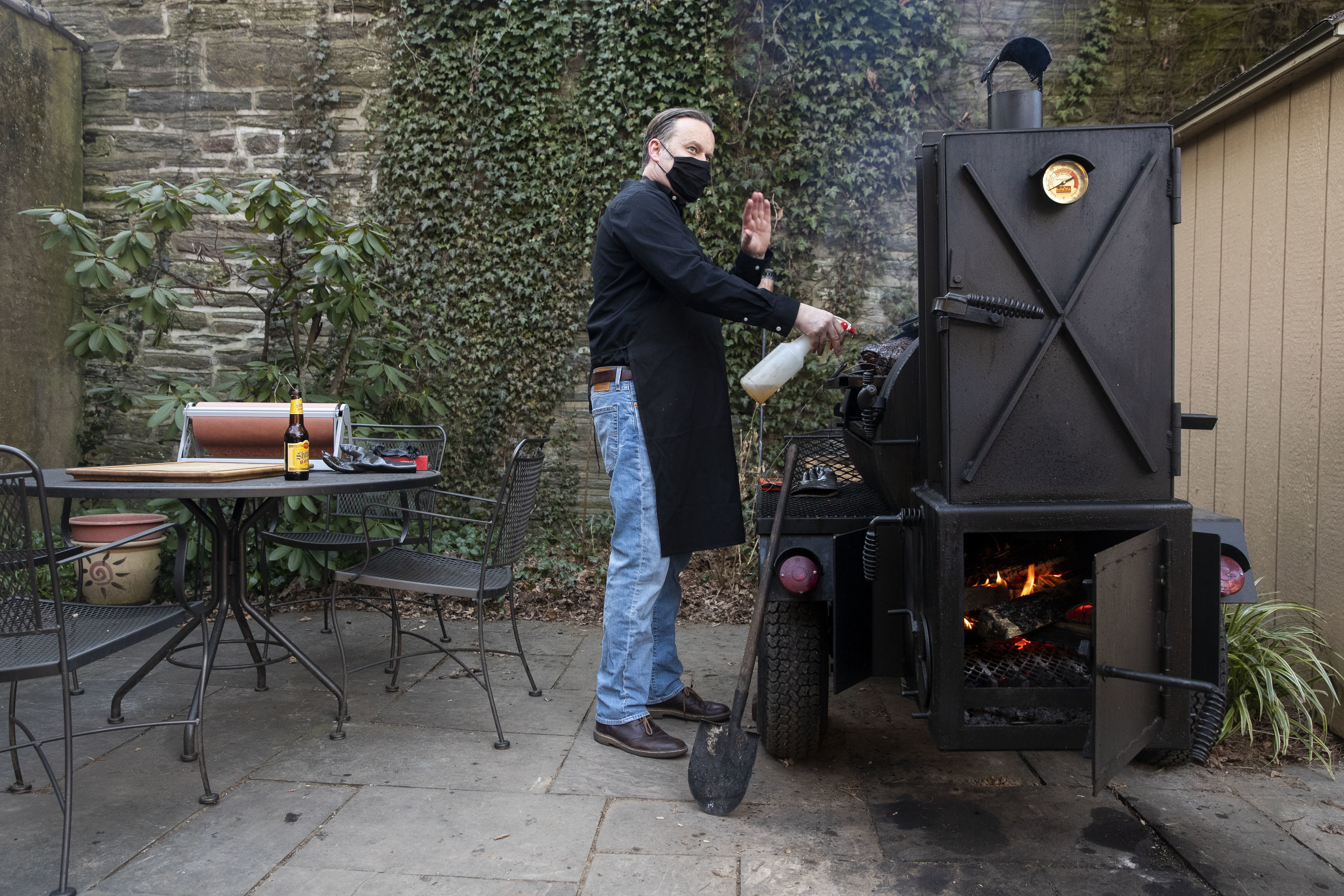 Scott Hanson sprays vinegar on the smoking meats in his backyard in the Chestnut Hill neighborhood of Philadelphia, Pa. on Sunday, March 14, 2021. Scott Hanson, a history and social justice professor, is launching a weekly pop-up collaboration with Cadence on March 21.