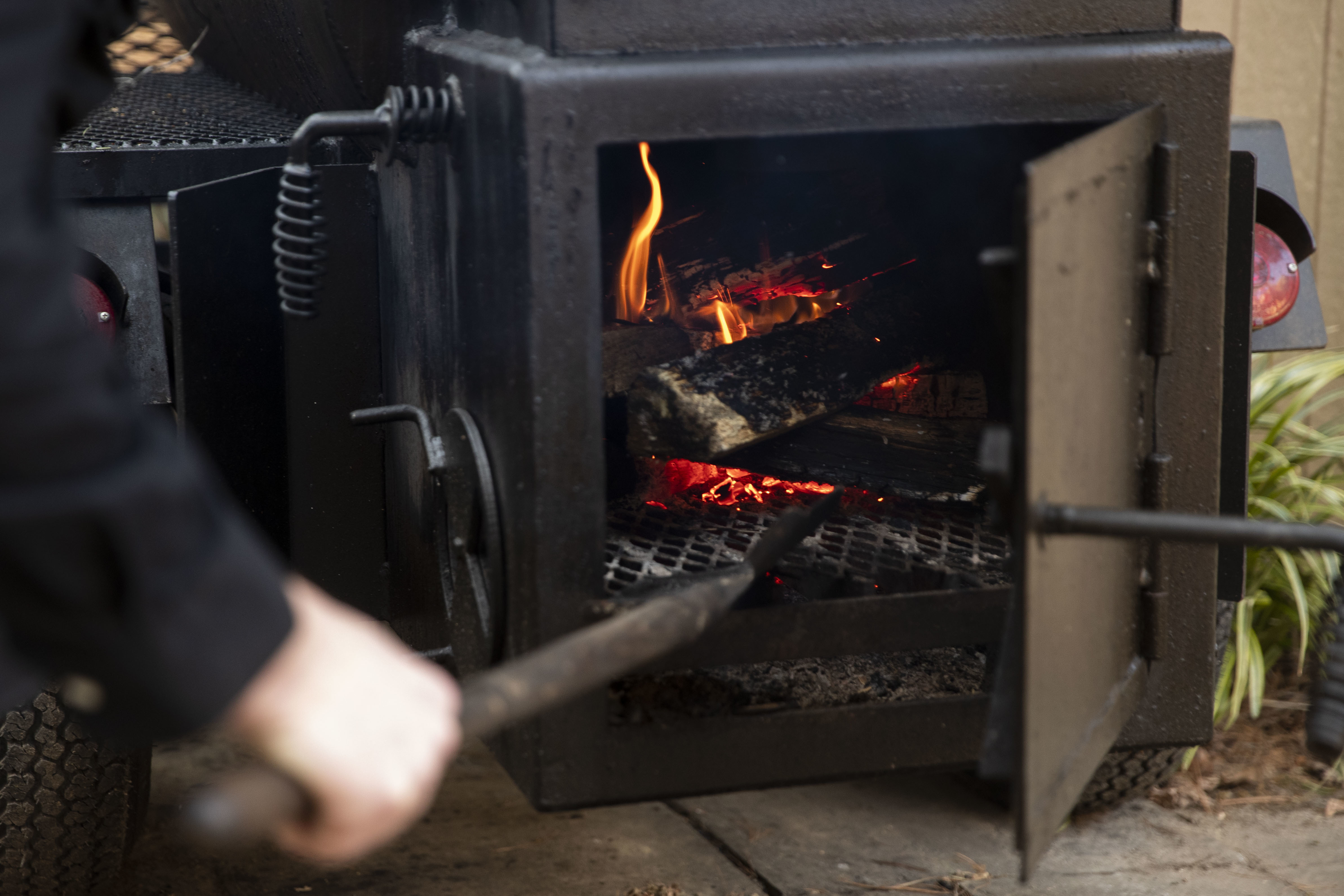 Scott Hanson stokes the fire in his smoker in his backyard in the Chestnut Hill neighborhood of Philadelphia, Pa. on Sunday, March 14, 2021. Scott Hanson, a history and social justice professor, is launching a weekly pop-up collaboration with Cadence on March 21.