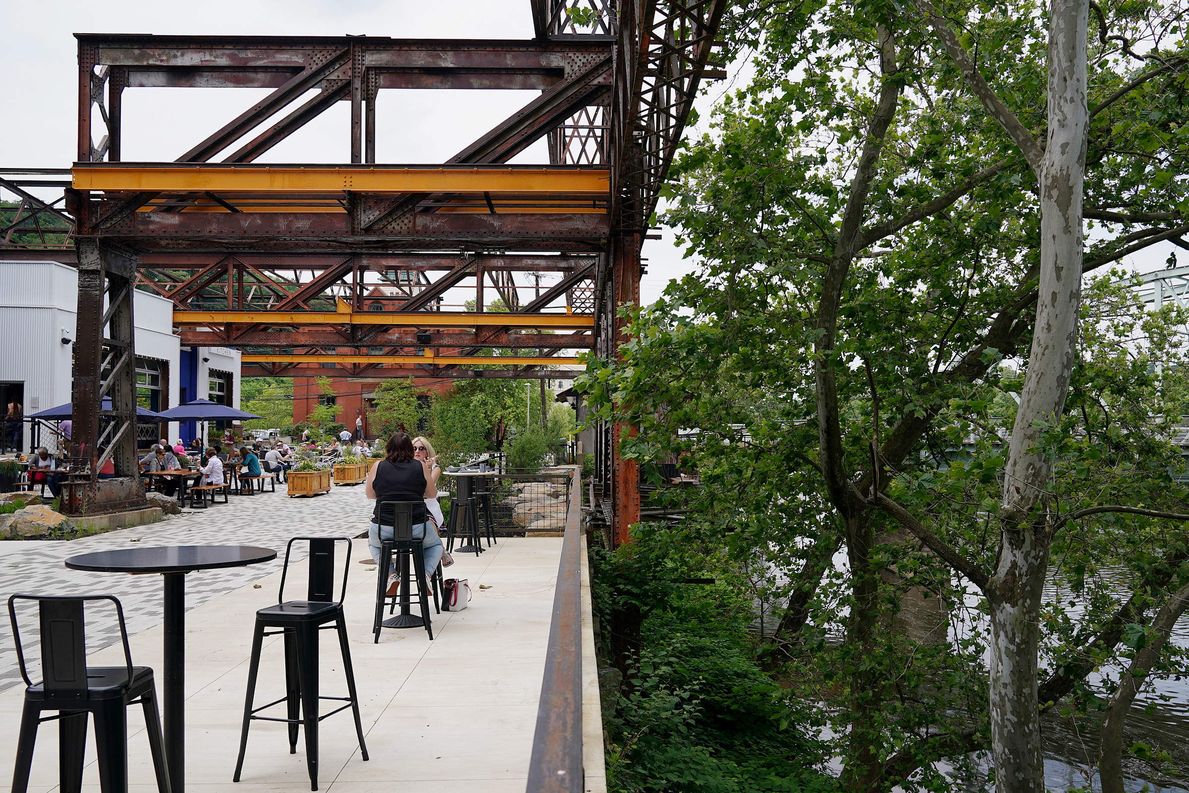 High tables line the river's edge at Pencoyd Landing. The Schuylkill's bank is much higher on the Lower Merion side than it is in Manayunk.