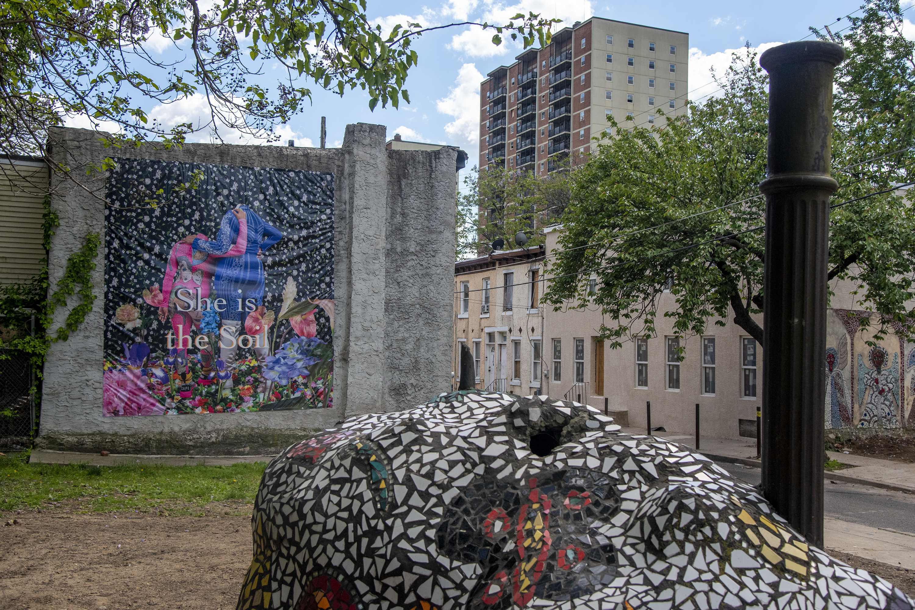 """One of four murals by artist Ebony G. Patterson, """"She Is..."""" presides over Ile Ife Park, next door to the Village of Arts and Humanities.  It reads, """"She is the soil."""""""