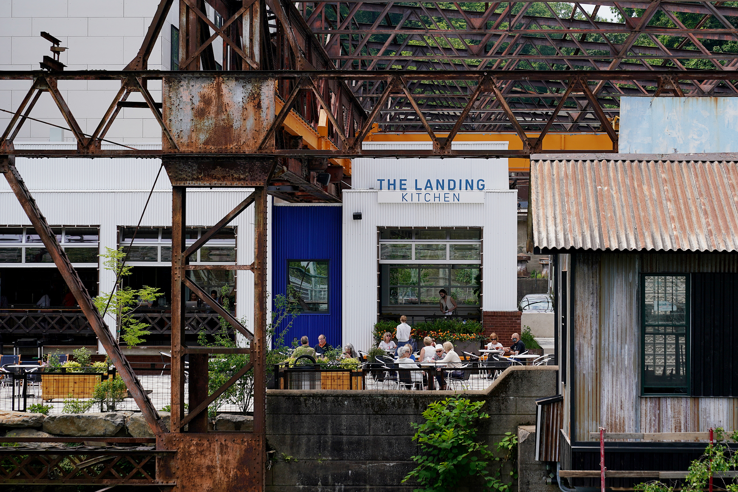 People eat at The Landing Kitchen restaurant at the Ironworks at Pencoyd Landing in Bala Cynwyd, Pa., on Wednesday, June 2, 2021. The new development, which opened earlier this year with a restaurant and hotel, is located on the site of the former Pencoyd Iron Works along the Schuylkill.