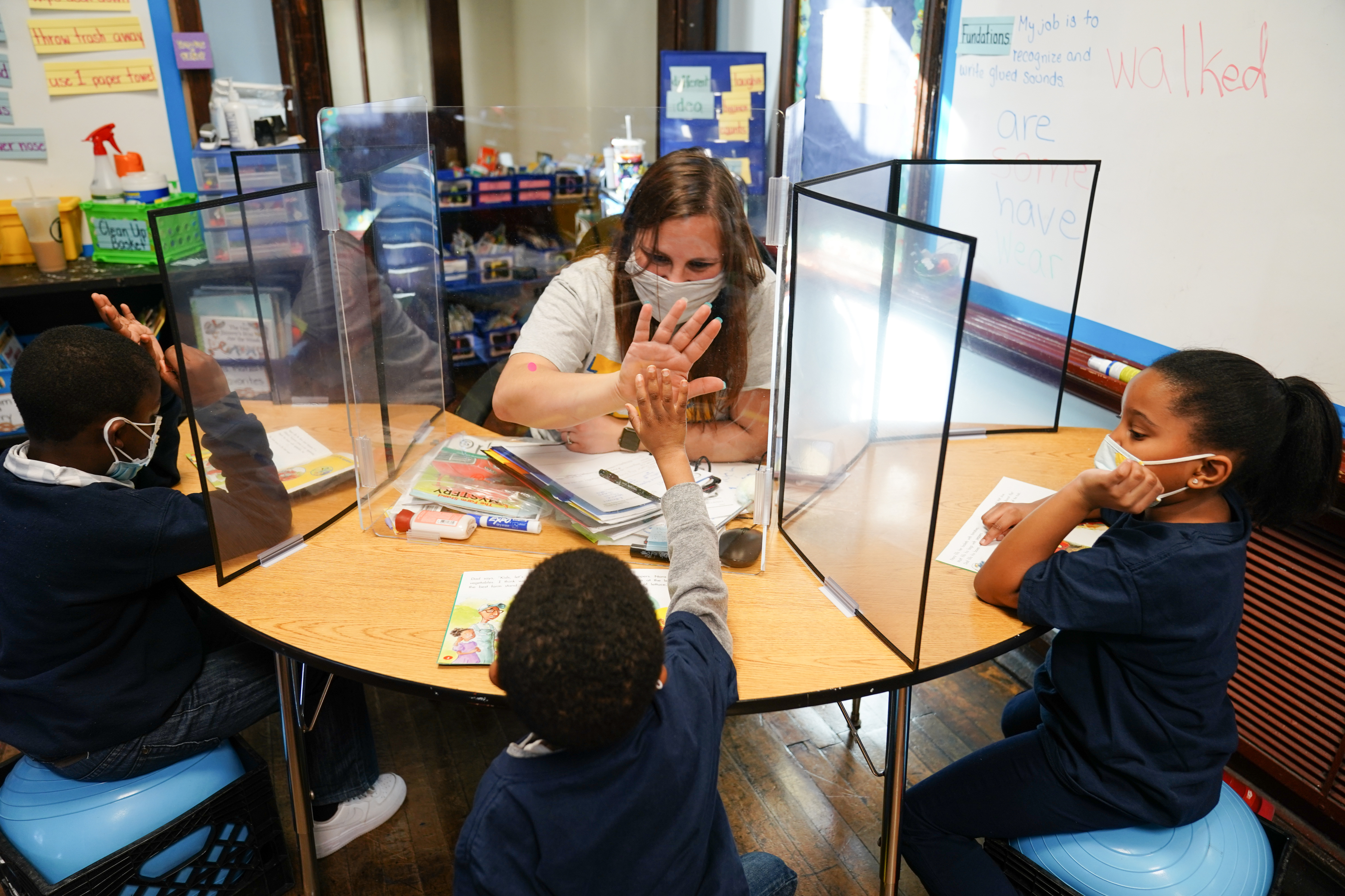 Michele Matza, back center, gives a high five to student Mershon Stevenson though a clear divider as she teaches at Belmont Charter School.