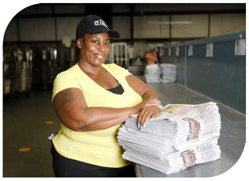 Female newspaper carrier with stack of newspaper.