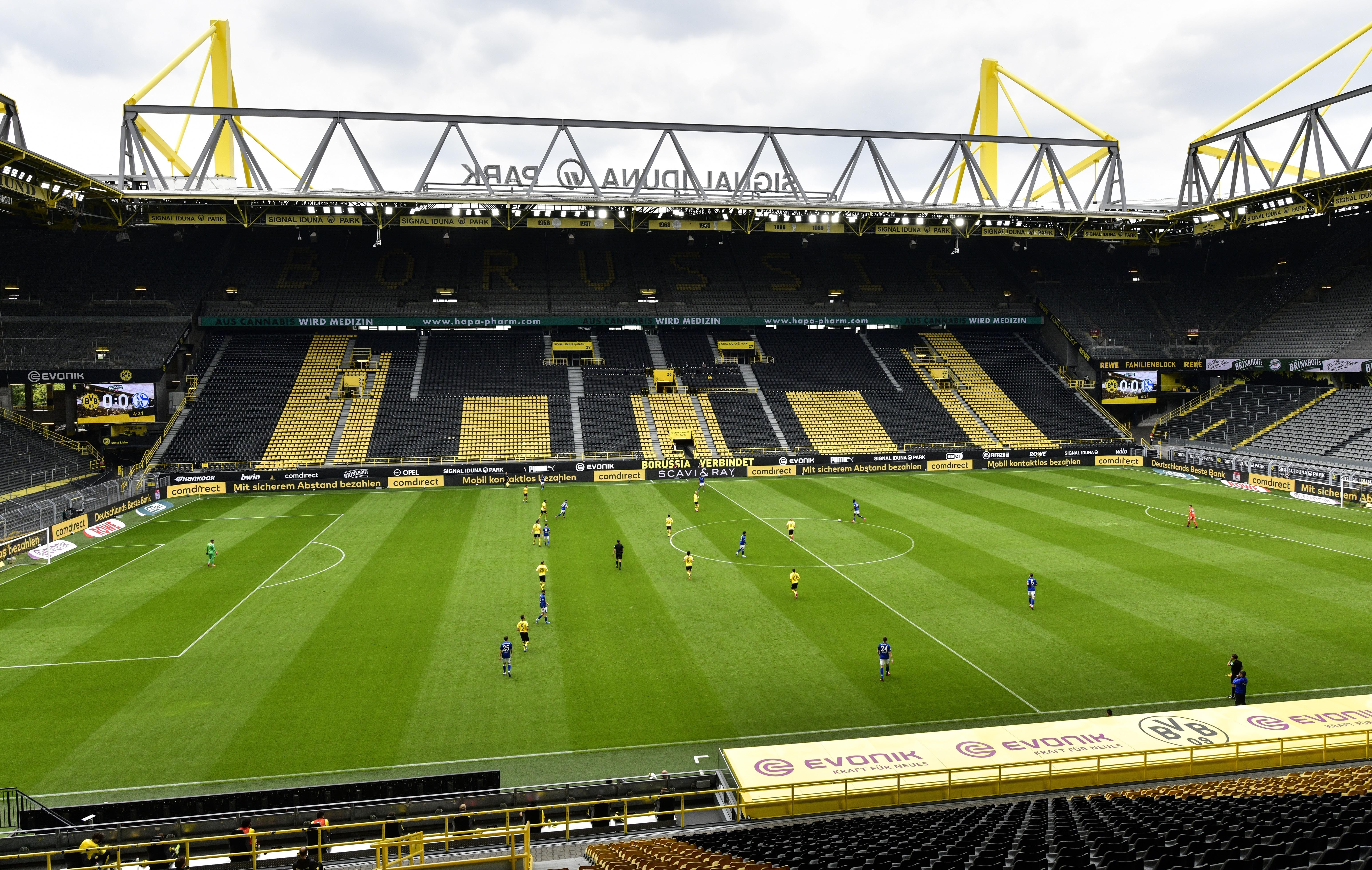 Empty seats are seen in the Signal Iduna Park without spectators during the German Bundesliga soccer match between Borussia Dortmund and Schalke 04 in Dortmund on  Saturday. The Bundesliga becomes the world's first major soccer league to resume plan after a two-month suspension because of the coronavirus pandemic. [HEINZ BUESE  |  AP]