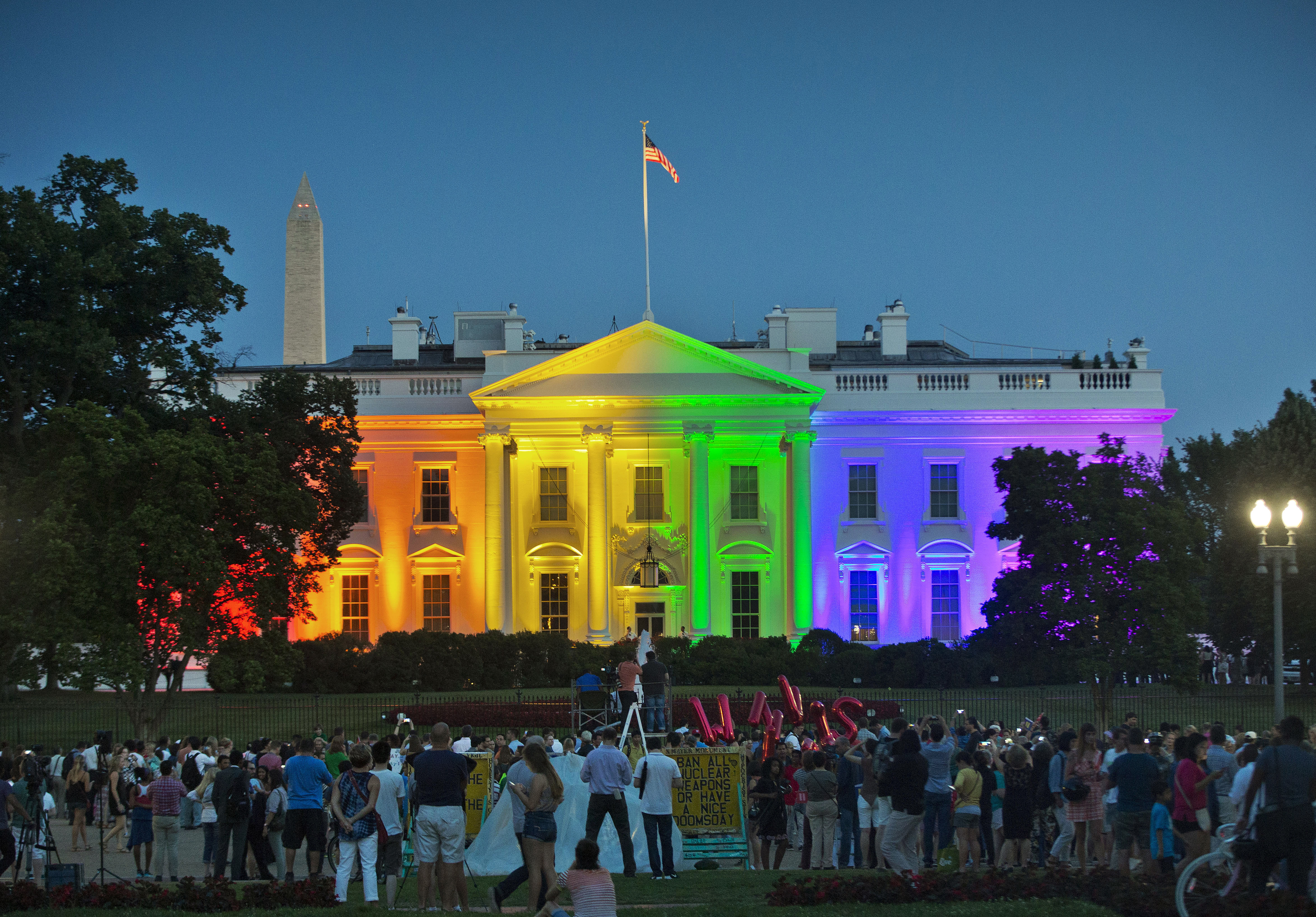 In this Friday, June 26, 2015 file photo, people gather in Lafayette Park to see the White House illuminated with rainbow colors in commemoration of the Supreme Court's ruling to legalize same-sex marriage in Washington. The Trump administration Friday, June 12, 2020, finalized a regulation that overturns Obama-era protections for transgender people against sex discrimination in health care. [PABLO MARTINEZ MONSIVAIS  |  AP]